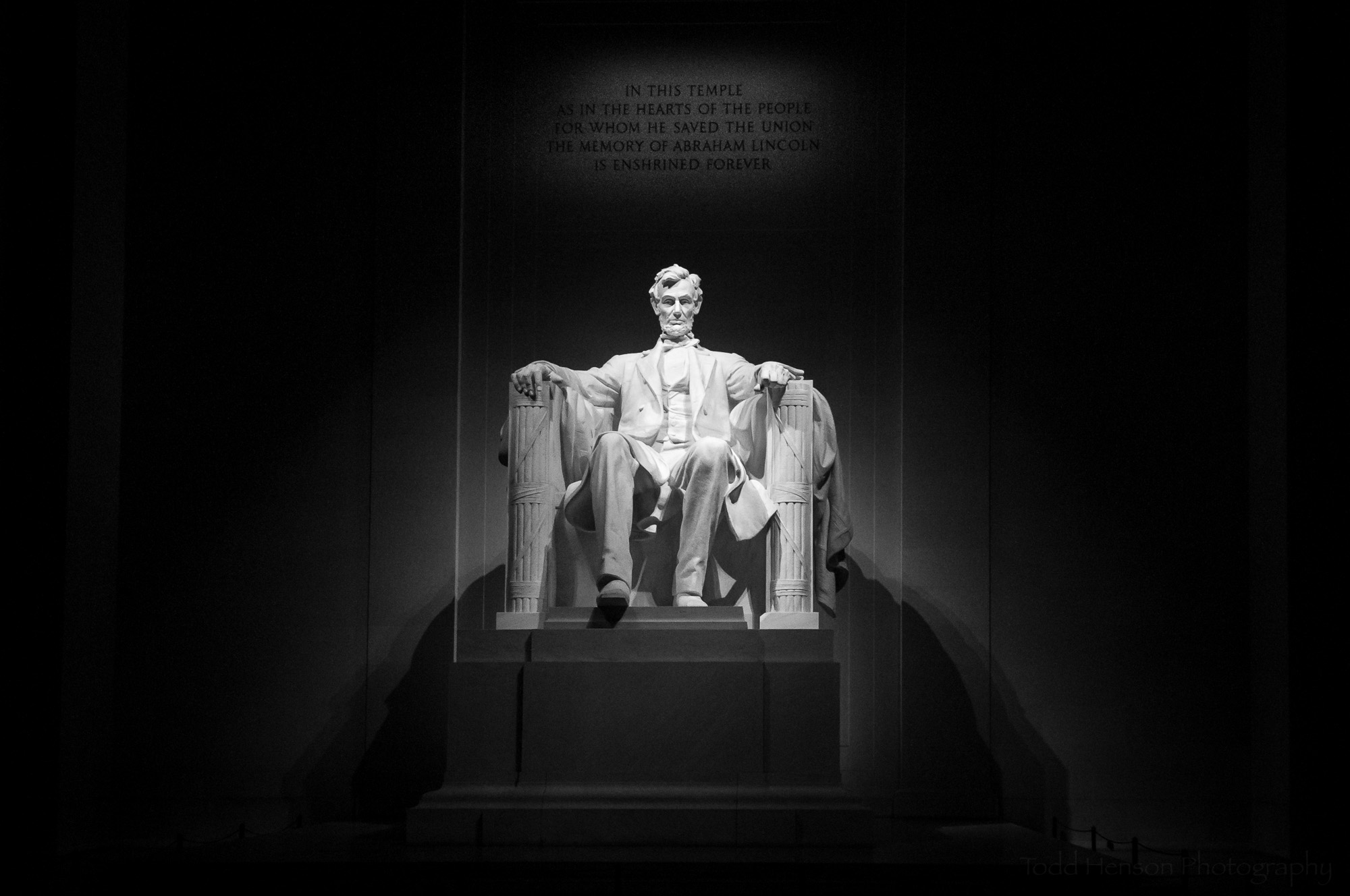 Black & white photo of the statue of Abraham Lincoln inside the Lincoln Memorial.
