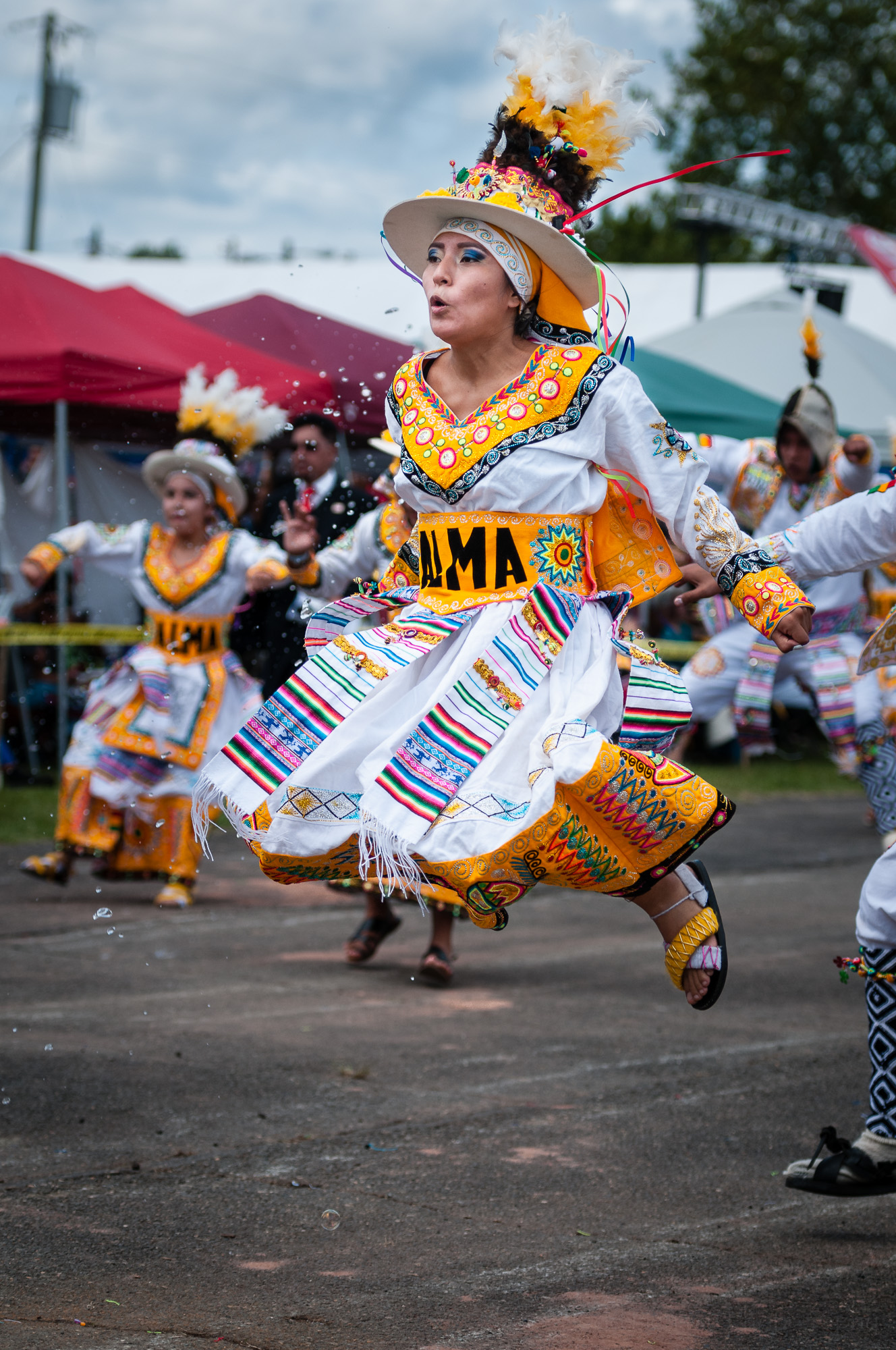 This member of Fraternidad Alma Boliviana showed such energy, jumping into the air during their performance of a Tinkus dance. Notice the water droplets to the side, splashed on the performers from folks walking alongside them, helping them cool down on the hot day.