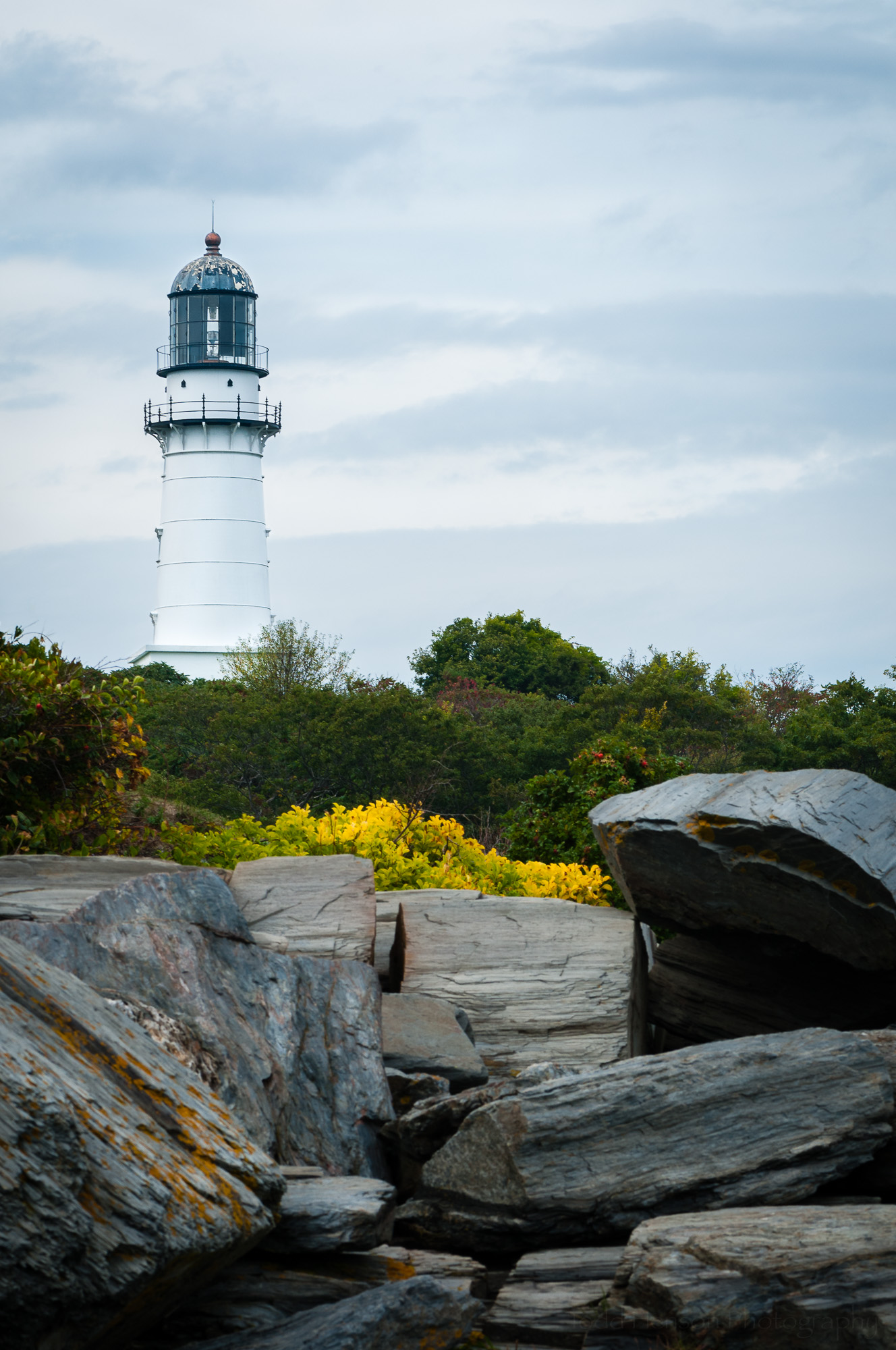The Eastern Tower of Cape Elizabeth Light (Two Lights), in Maine, seen from rocky shore