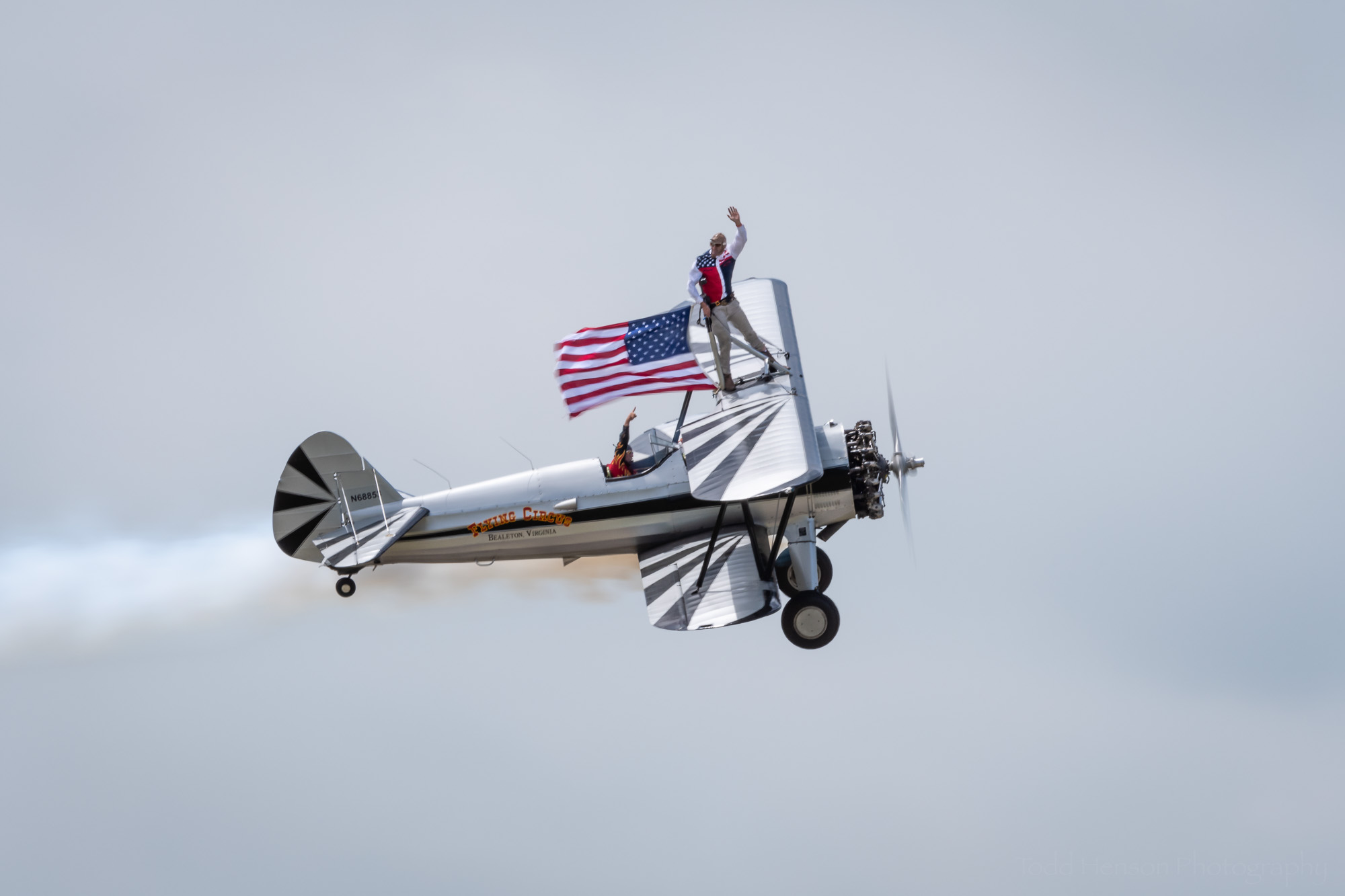 Chuck Tippett and Joe Bender of the Bealeton Flying Circus flying a US flag atop their Stearman biplane.