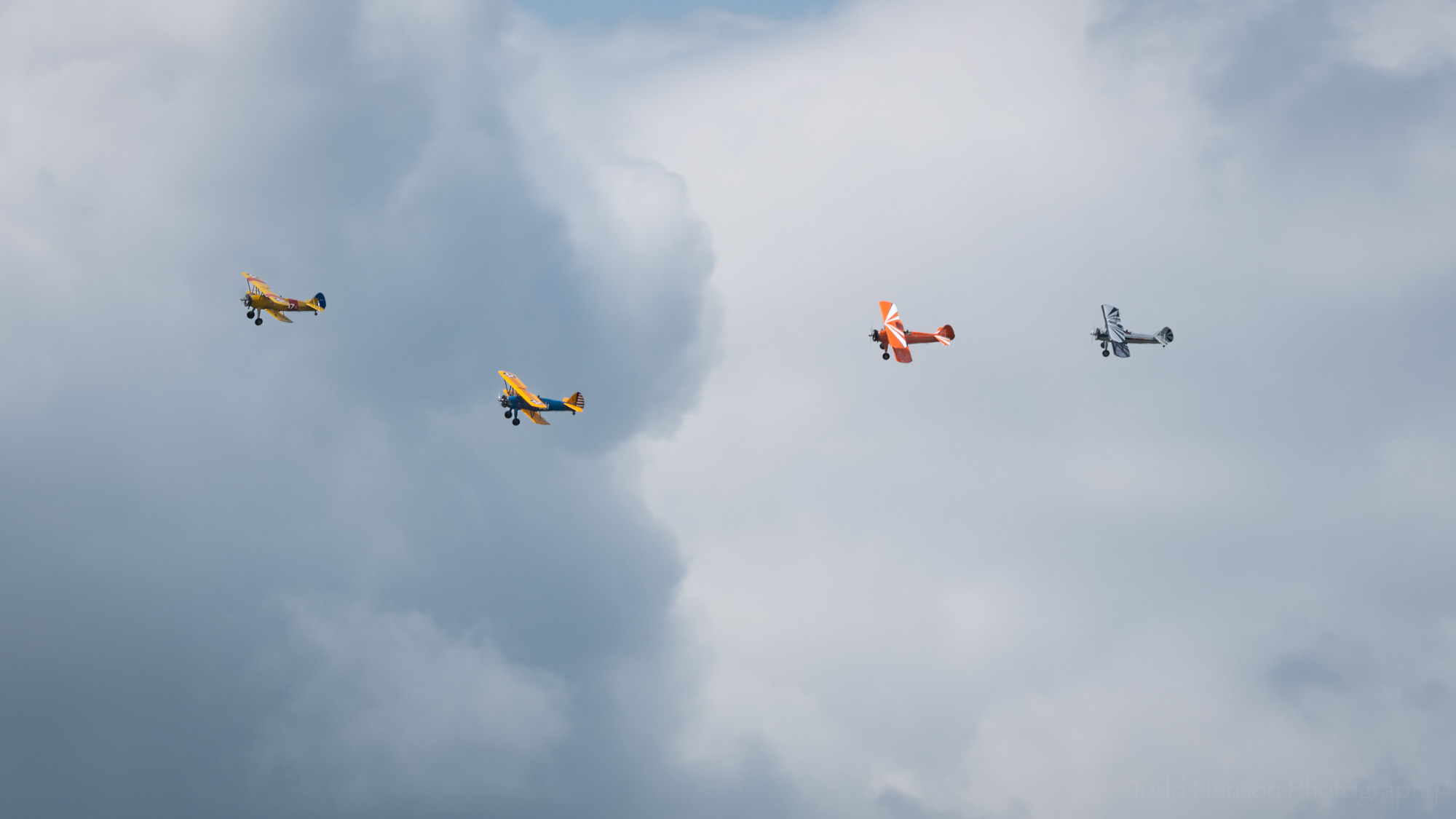 Four biplanes from the Bealeton Flying Circus flying in formation against the cloudy sky.