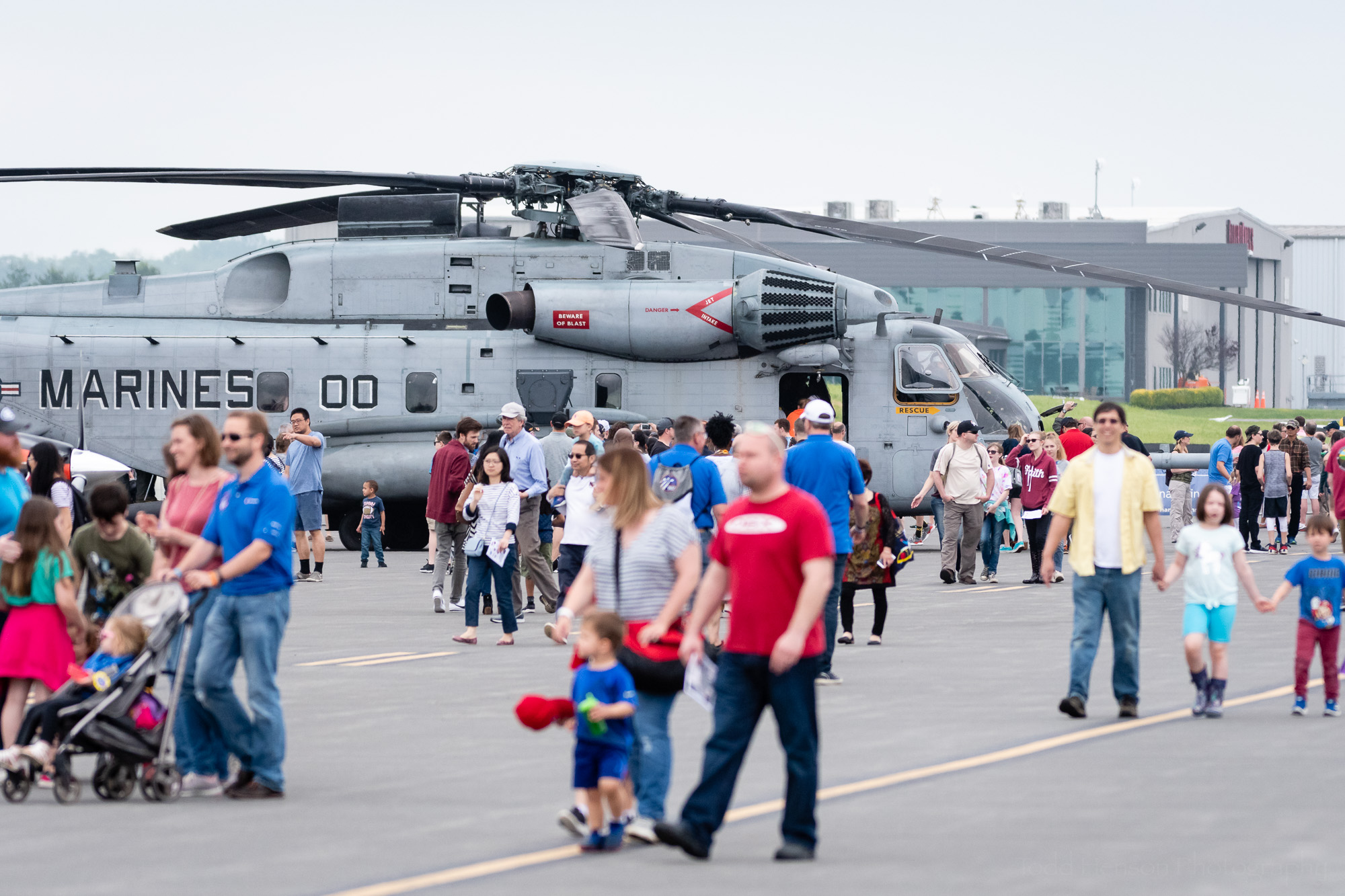 Crowds walking around the 2019 Manassas Airshow, with a US Marine Super Stallion CH-53 helicopter in the background.