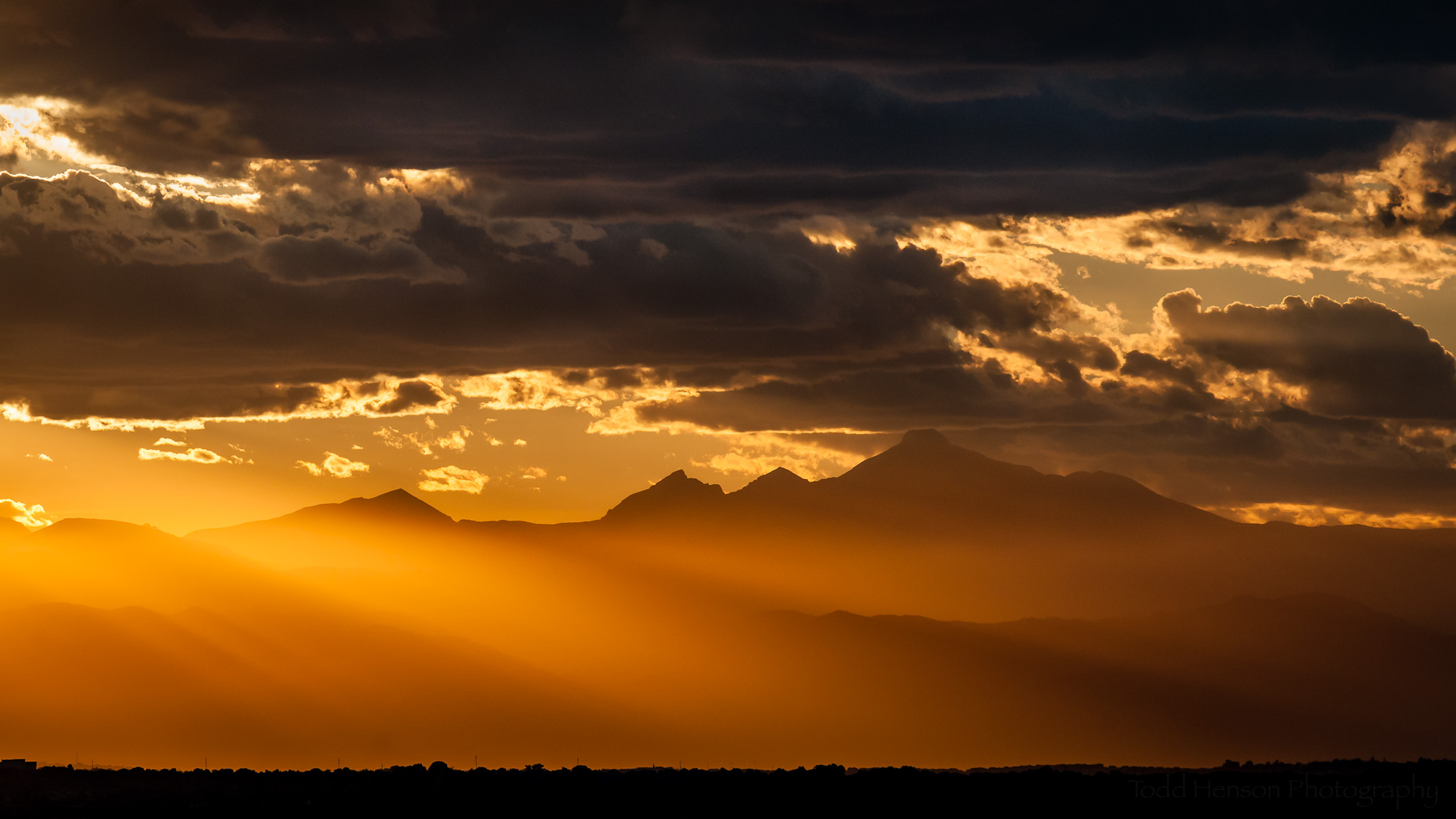 Rocky Mountain Sunset . The setting sun turns the Rocky Mountains into dark silhouettes engulfed in a soft orange glow.