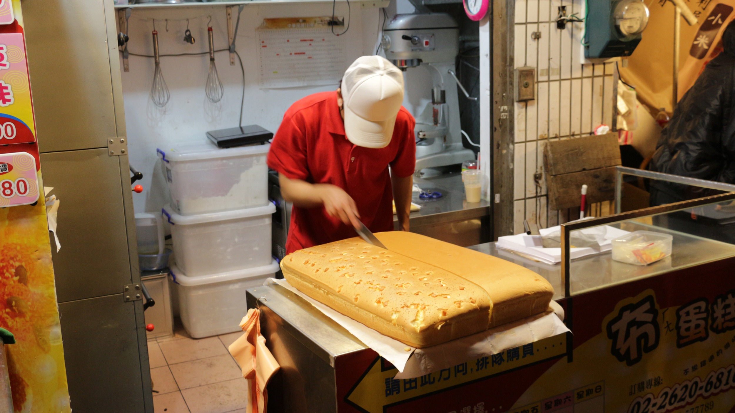 "Tamsui sits at the end of the red line outside of Taipei. It's a place for gathering and is located right on the river with a night market running along the riverbank.  While there, my girlfriend ordered this cake for us - ""traditional Taiwanese cake"".  This moment captured the first cut where they separate the plain half from the cheese filled half.  Even though the cuts of cake are quite large, we went through it very quickly.  It's very thick and spongey cake and not too sweet.  Delicious."