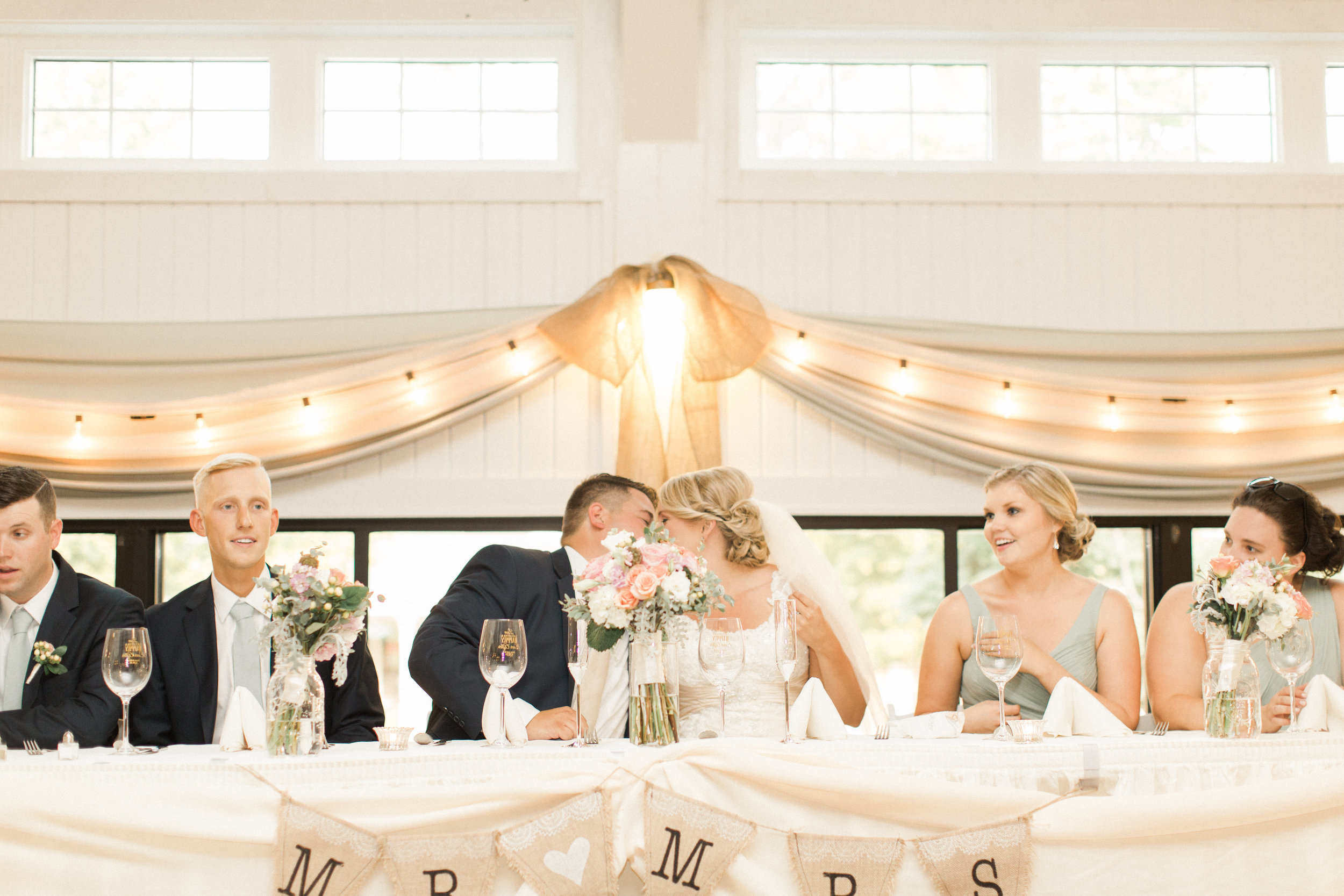 head-table-white-lights-pink-flowers-flags-bride-groom-kiss