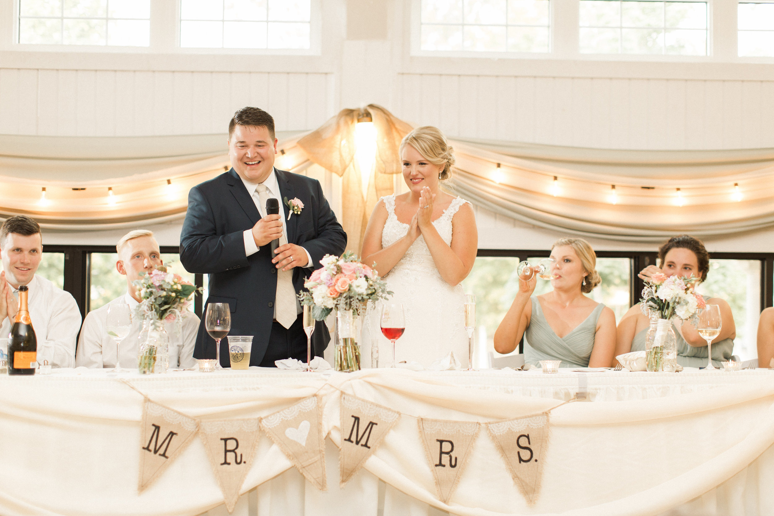 head-table-toasts-okoboji-iowa-wedding-reception-white-lights