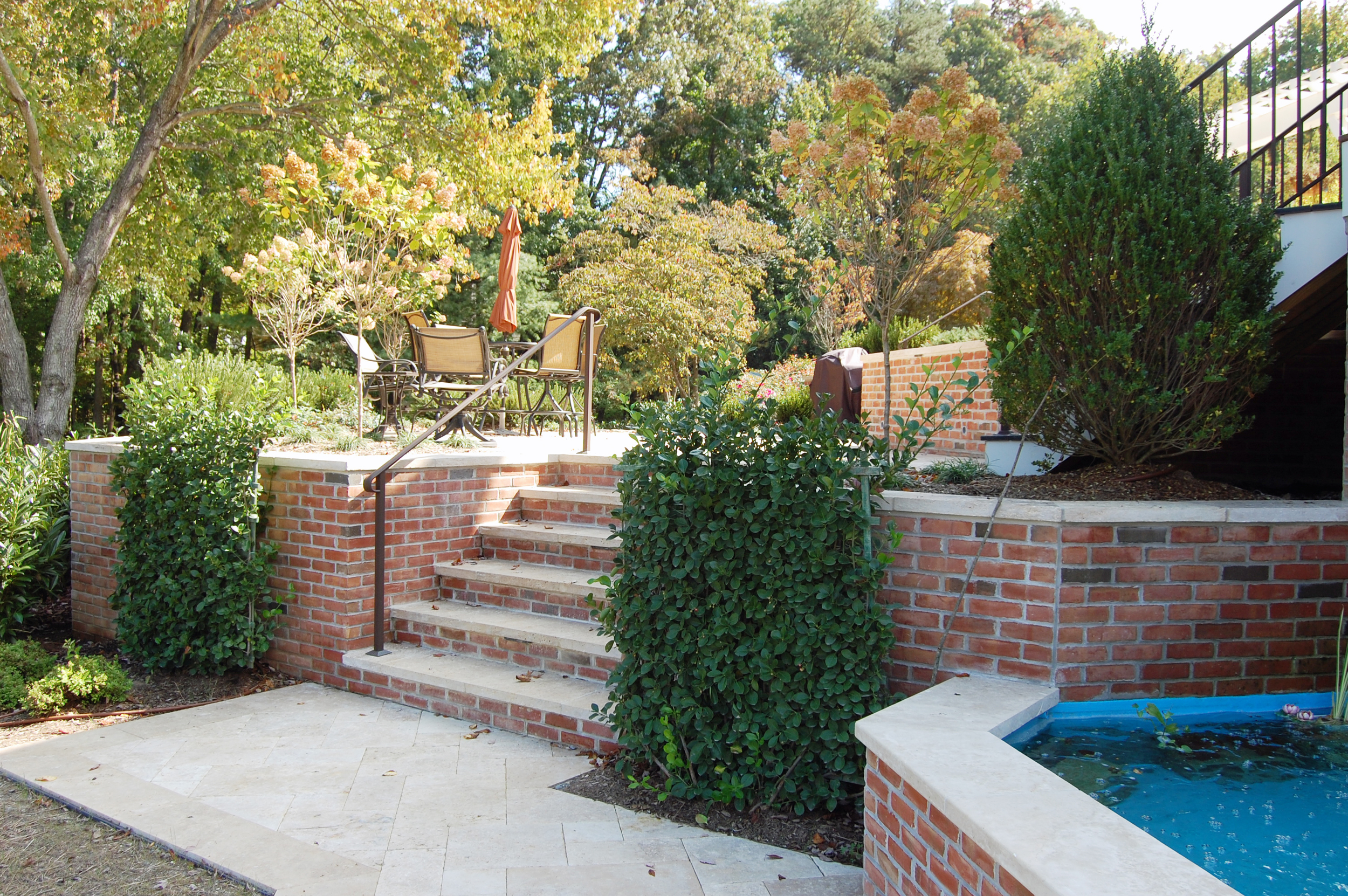 Brick walls and travertine step landings to the lower level.