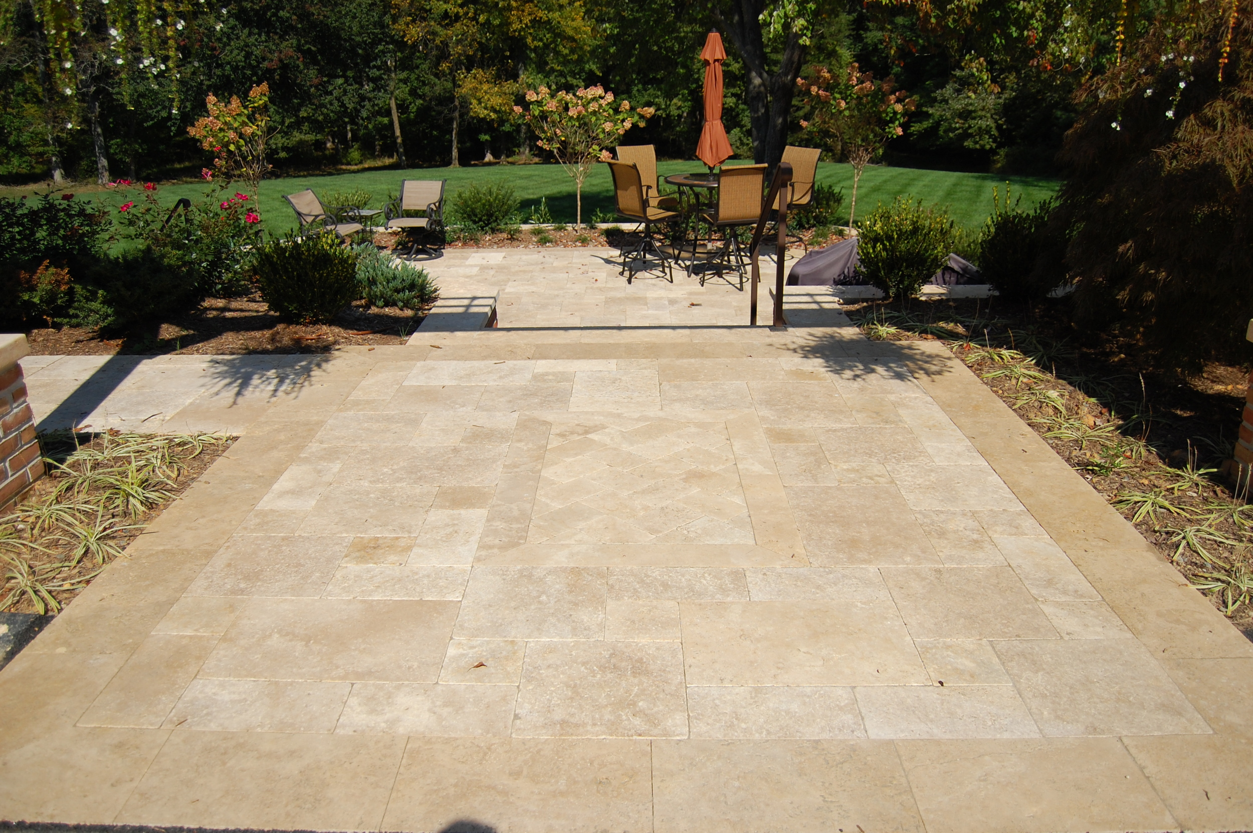 Travertine terraces and landings create extra space and a gradual step down from the second story deck.