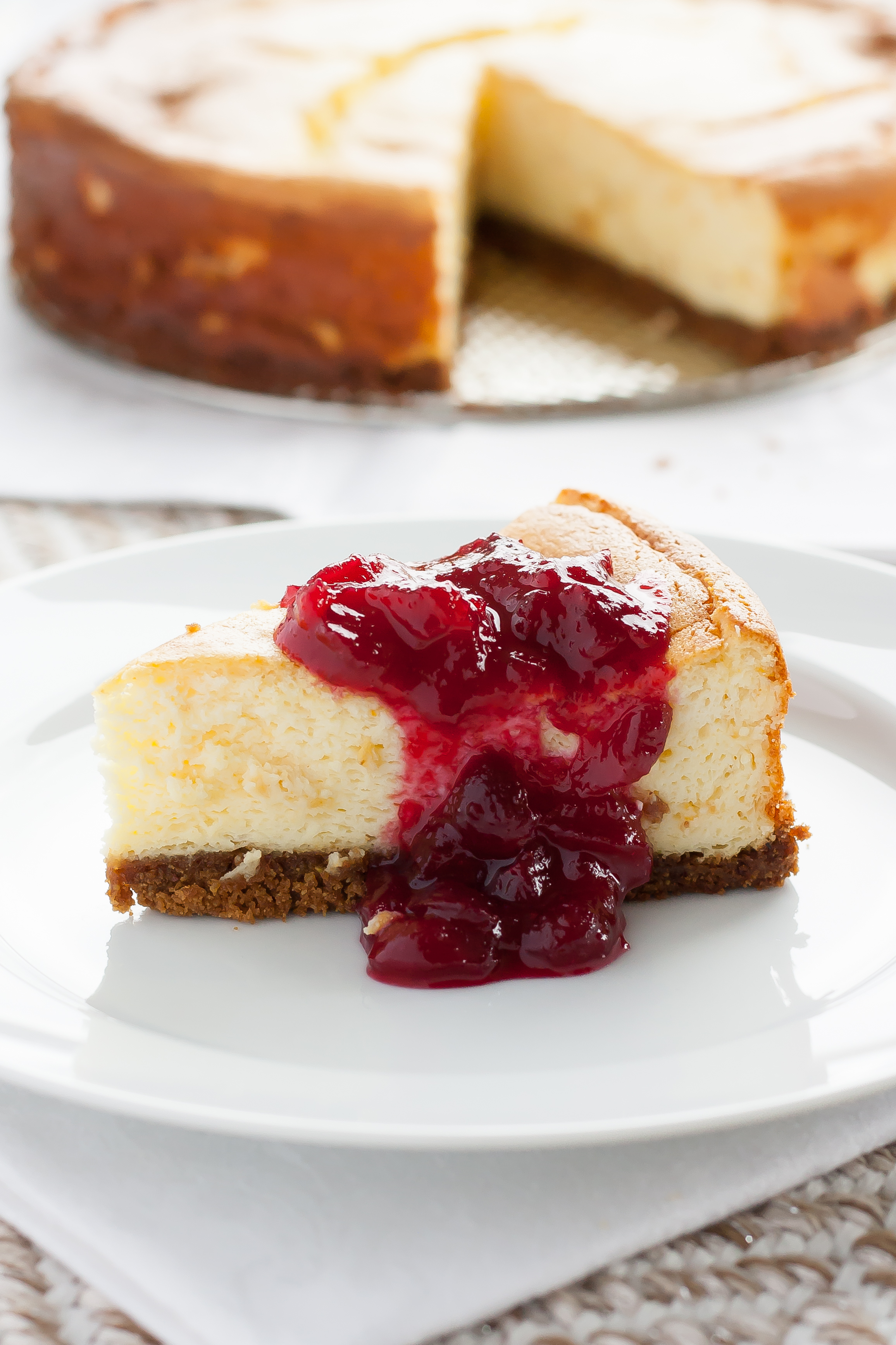 ricotta cheesecake with ginger snap pistachio crust and cranberry orange sauce