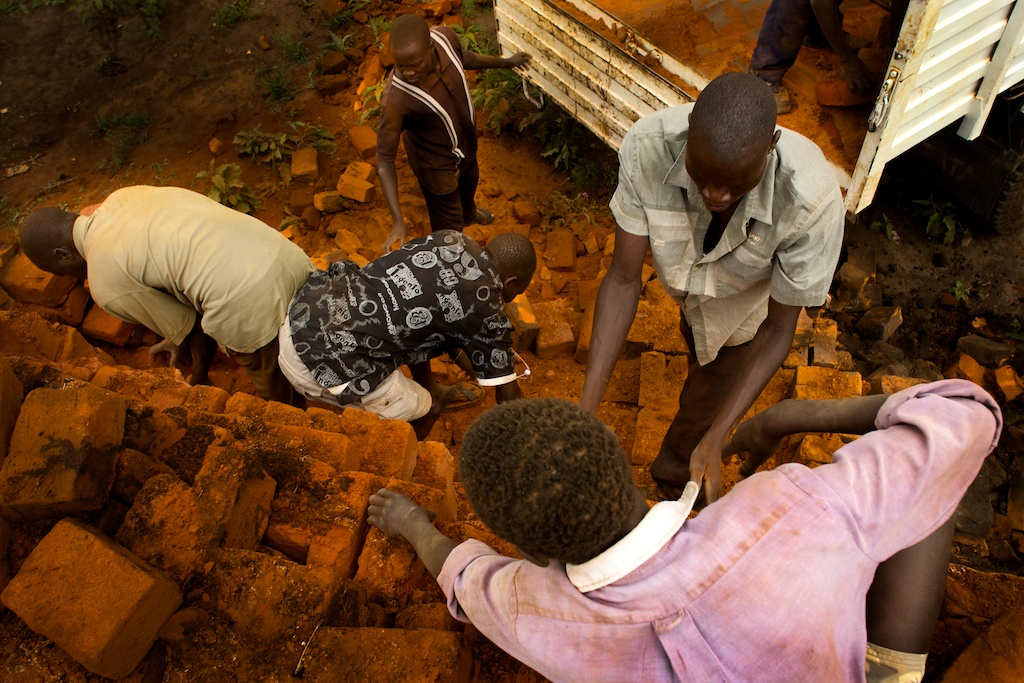 Karamoja workers transfer bricks onto a truck from a kiln pile near Kaabong, Uganda.