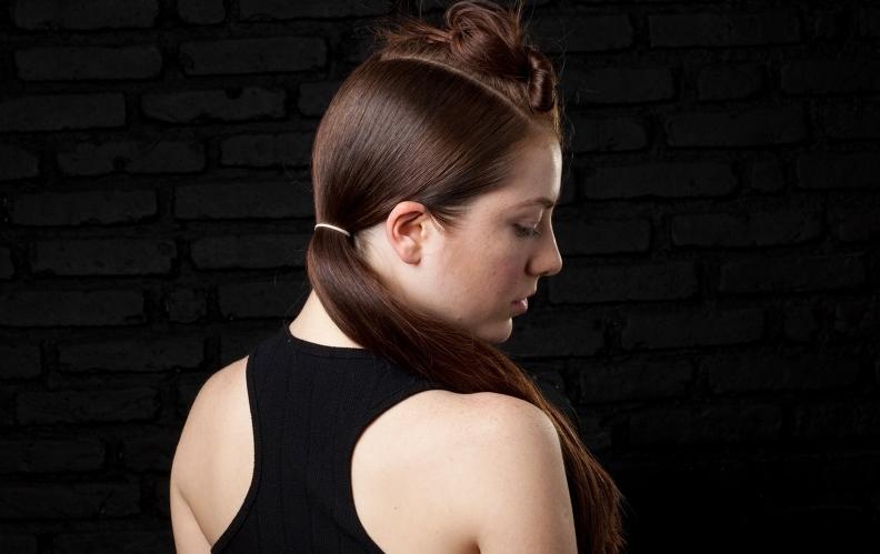 Aplique um pouco de cera no restante do cabelo para eliminar o frizz e, com o pente fino, penteie as mechas para baixo. Prenda o rabo de cavalo baixo lateralmente com a ajuda de um elástico