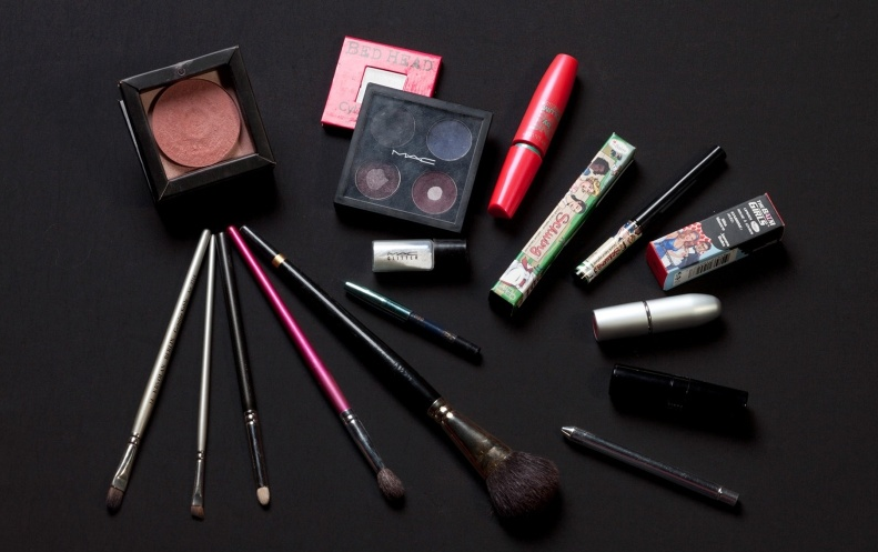 Na hora de fazer a maquiagem, você vai precisar de: base, sombra azul escura, prata, marrom e marrom acinzentada, lápis preto, iluminador, delineador preto, máscara para cílios, blush com tom de rosa velho, batom vermelho e vinho e pincéis para maquiagem