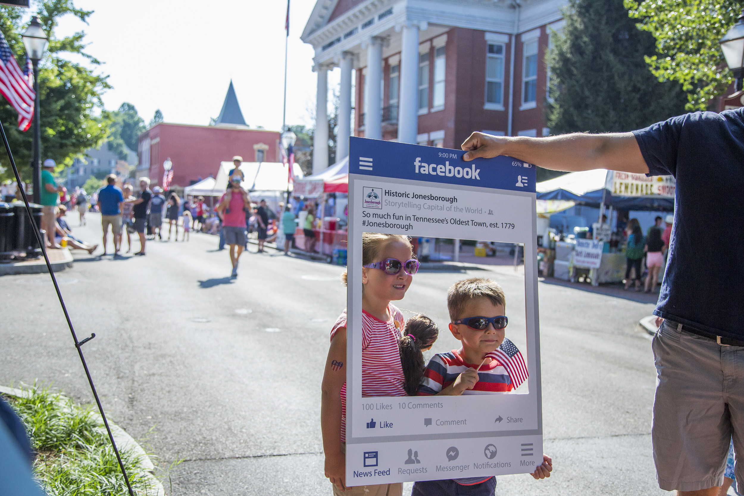 Children pose for a picture through a mock-post Facebook frame for Historic Jonesborough.