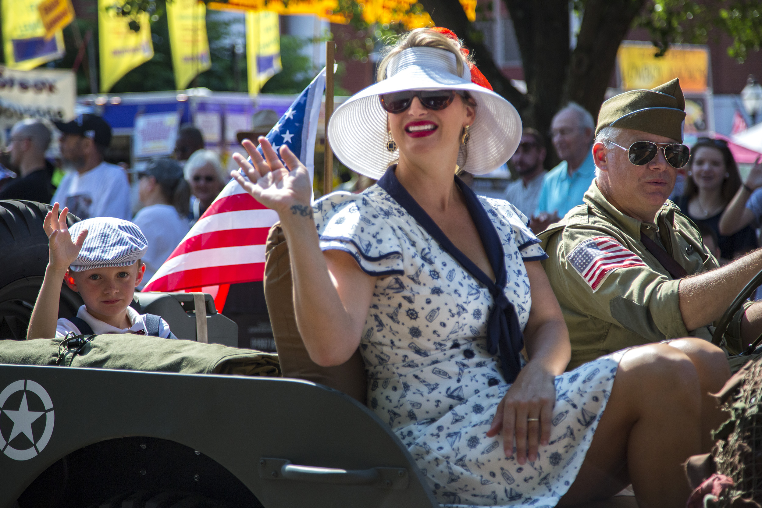 A family dressed in 1940's outfits and an American Flag attached to their car waves at the crowd.
