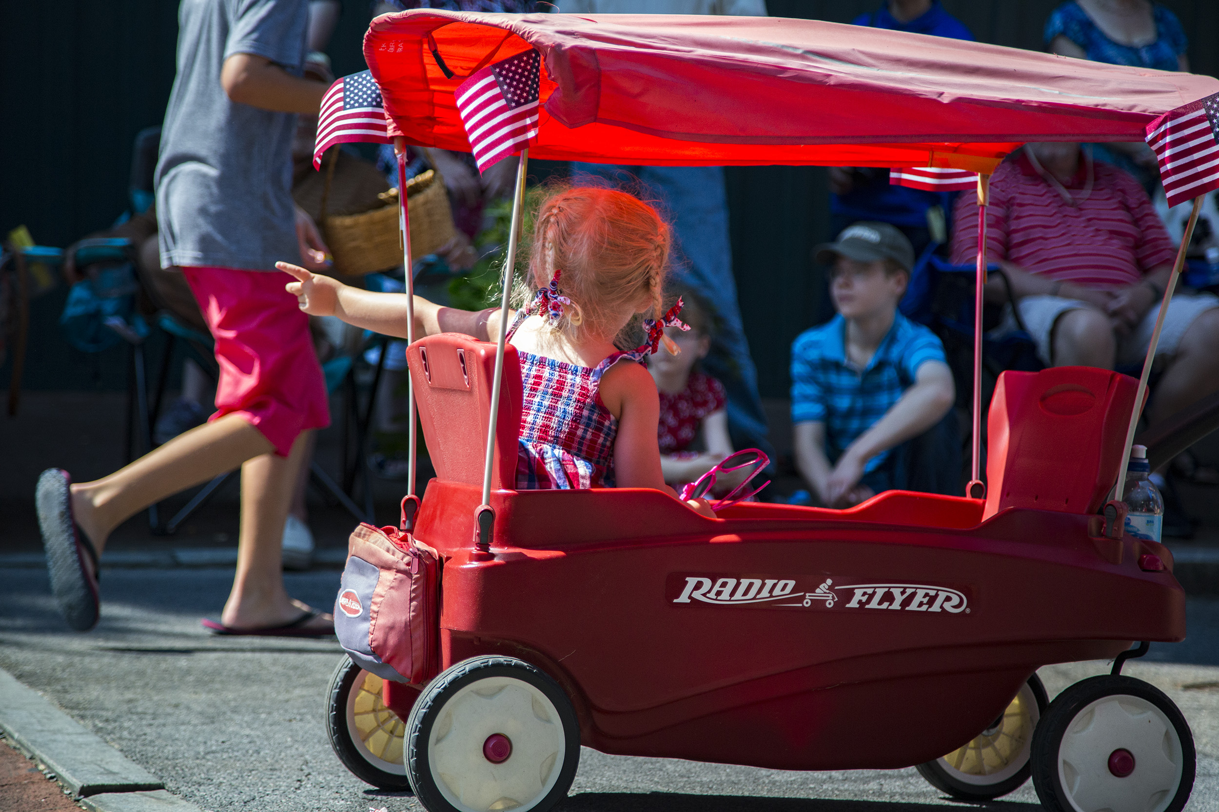 A red, white and blue adorned girl, in a Radio Flyer,points to a photographer for the local paper. Jonesborough, Tennessee.
