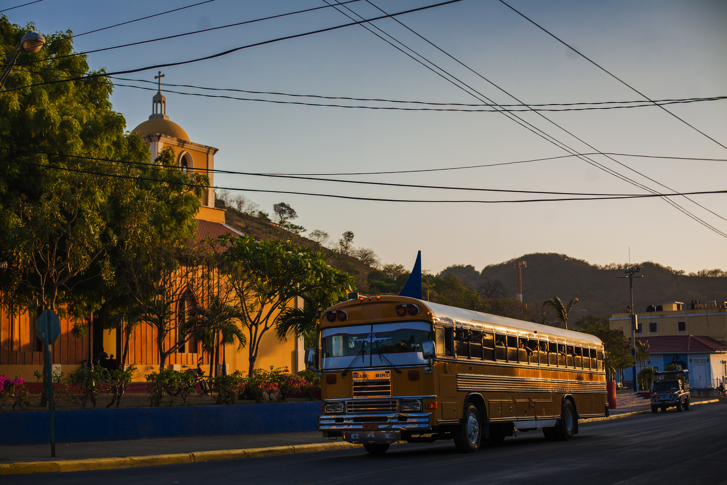"""Yellow """"Chicken bus"""" in front of the church in San Juan"""