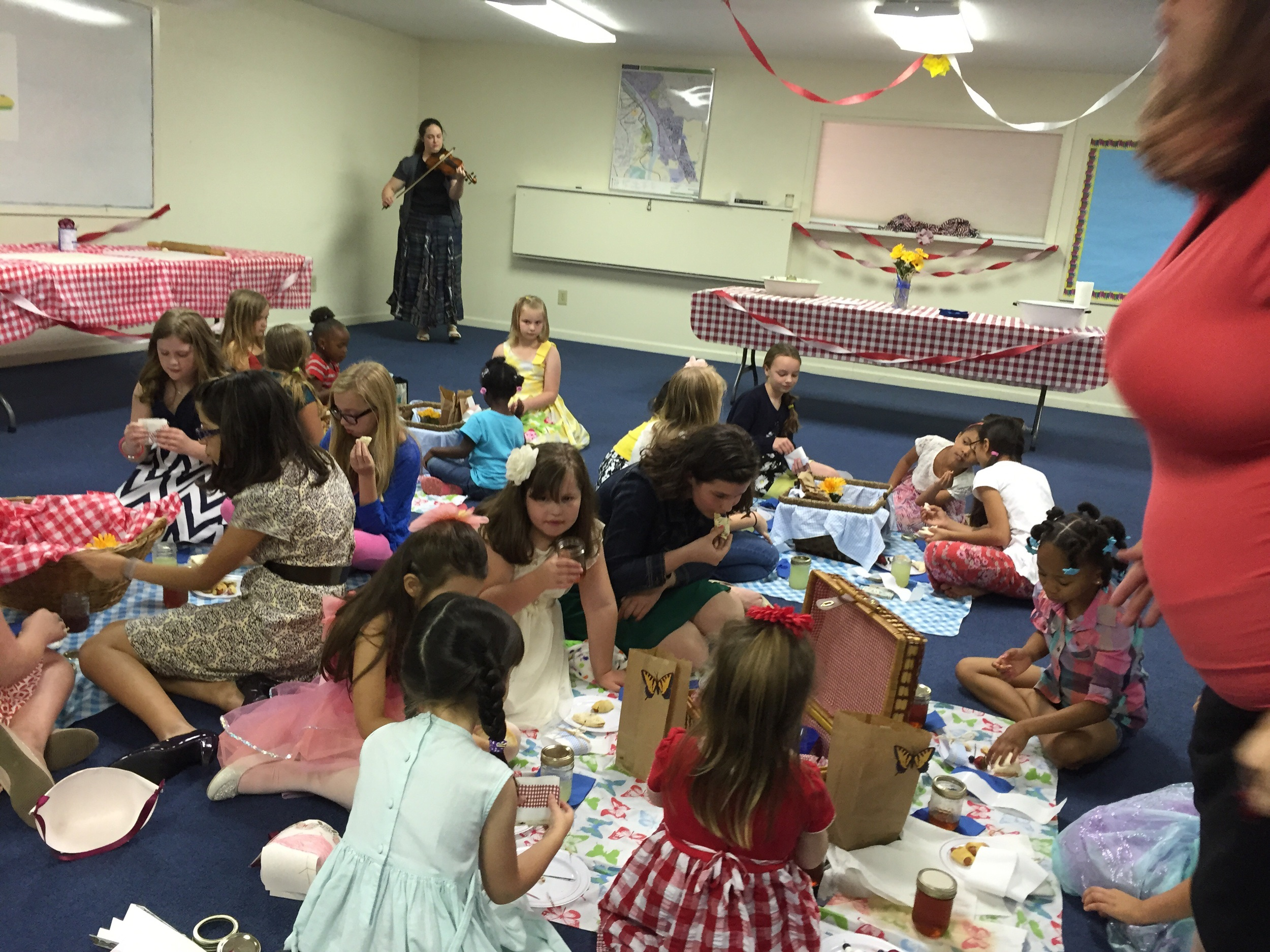 All of the girls enjoying a pioneer tea party with live fiddle music!