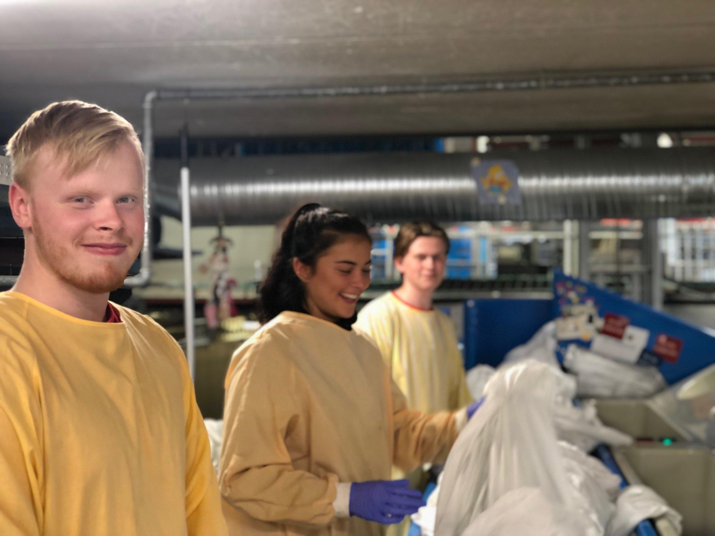 Her står Tobias (til venstre) og Kimmely (i midten) og sorterer laken som skal sorteres før vask.