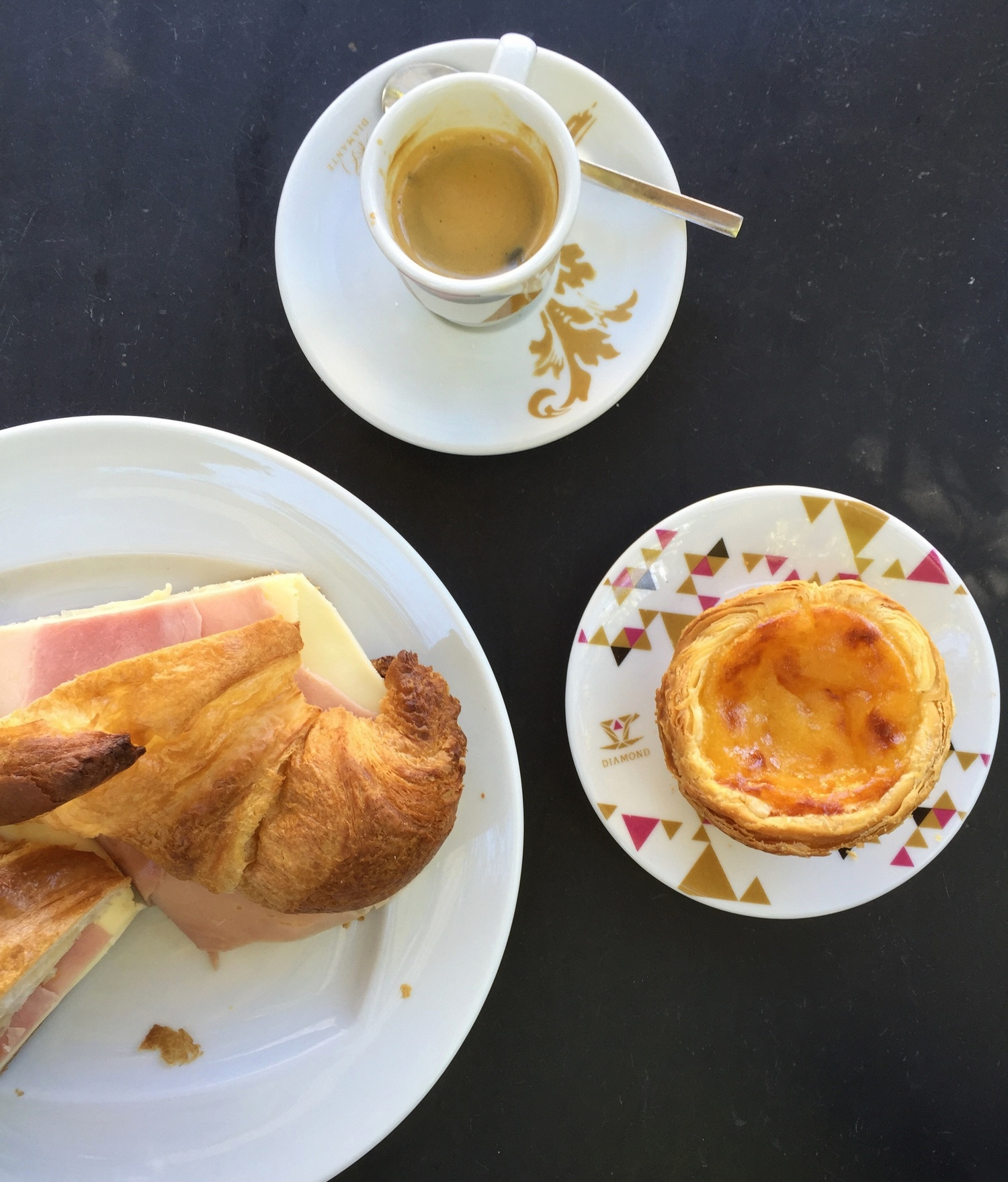 Espresso, pastel de nata with a sprinkle of cinnamon, and a ham and cheese croissant. Portuguese cheese is some of the best I've ever tasted.