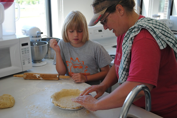 Ashley Kern watches instructor Lois Schulz pinches the crust into the pan.