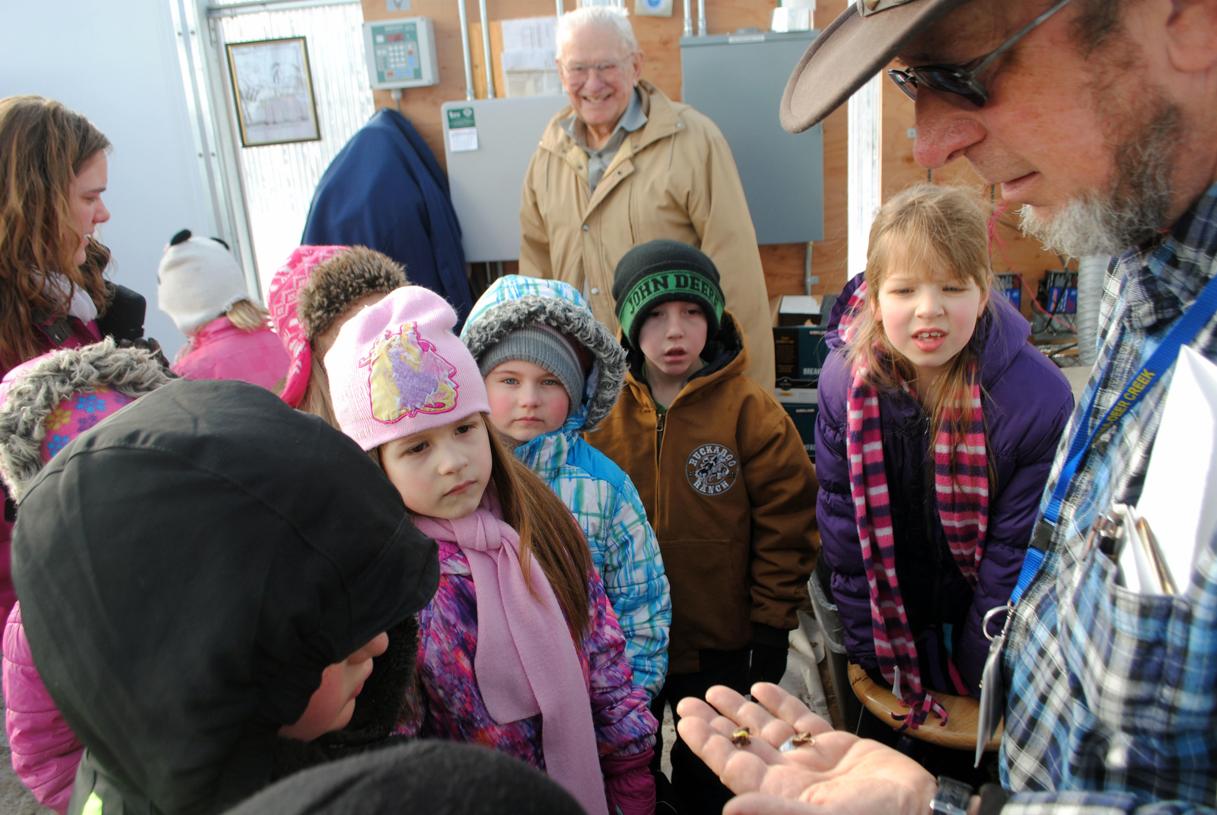 Greenhouse caretaker Ed Lewis shows the inquisitive first-grade students bean seeds that have germinated. (Photo by Dana Pavek, WDC Schools)