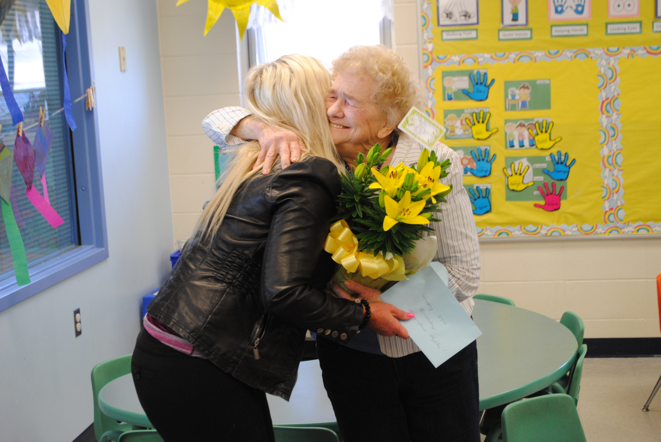 Phyllis Jackson, right, gives Kids Club Director, Tracy Dreger, a big hug after she received a beautiful day lily and birthday card from staff on Thursday.