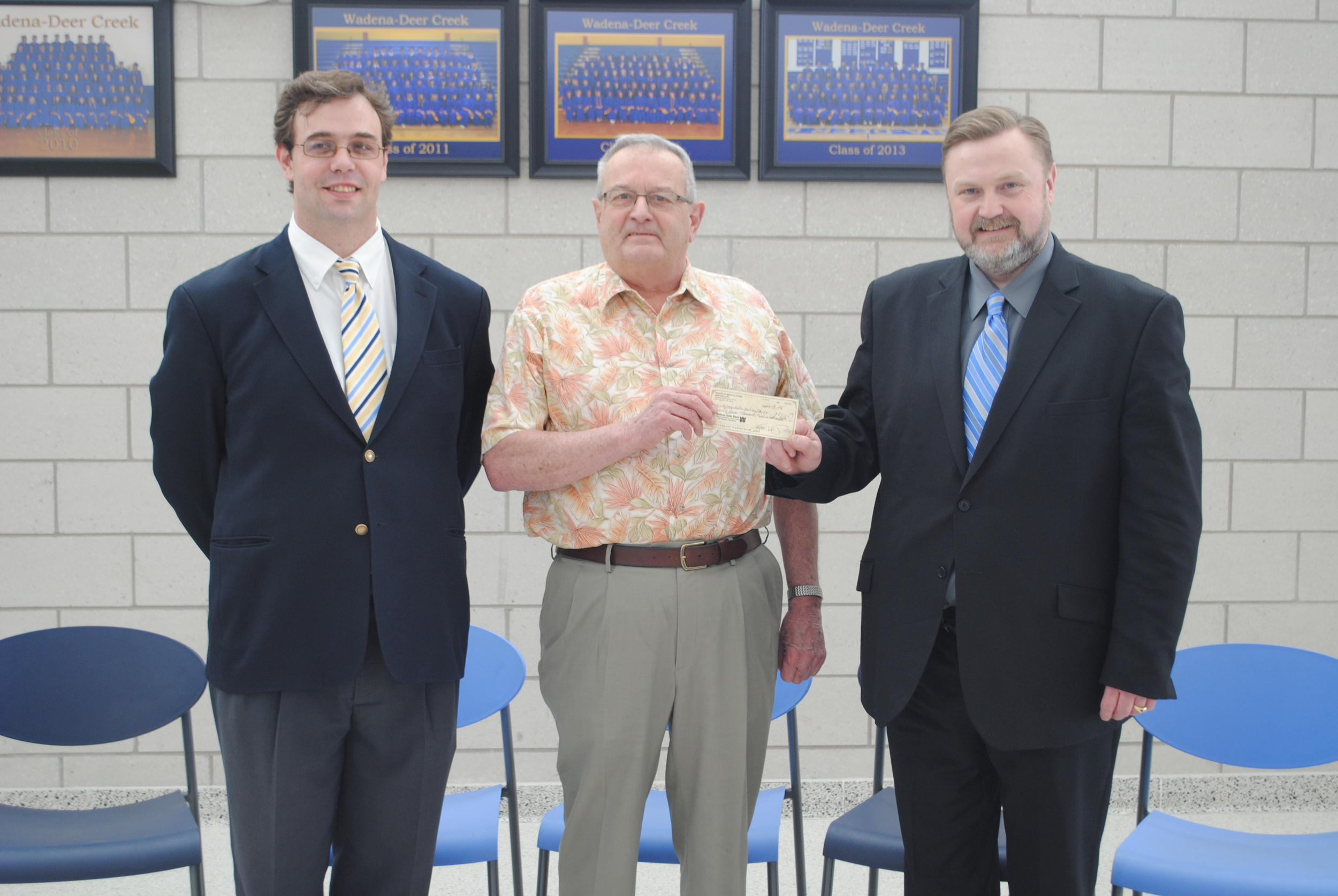 Sam Phillips hands WDC Superintendent Lee Westrum a gift from the estate of Betty Stark on April 9 at WDC Middle/High School. Also pictured is Malcolm Whynott, the attorney who assisted with the distribution of gifts. (Photo by Dana Pavek, WDC Schools)
