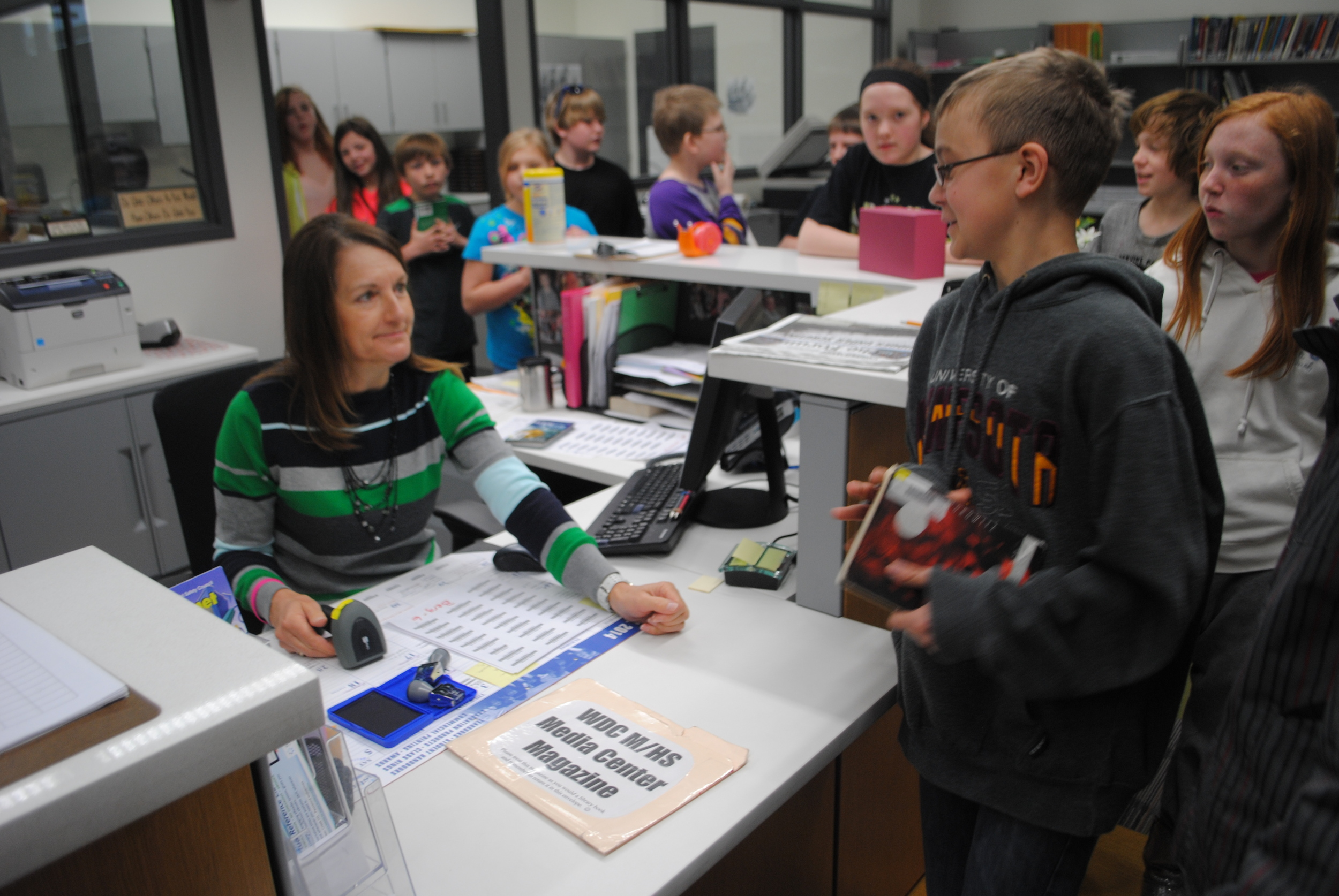 Media Center assistant Kathie Davis takes care of a long line of sixth-grade students from Mrs. Berg's class on Tuesday. Mrs. Davis takes time to chat with students as they return or check out books.