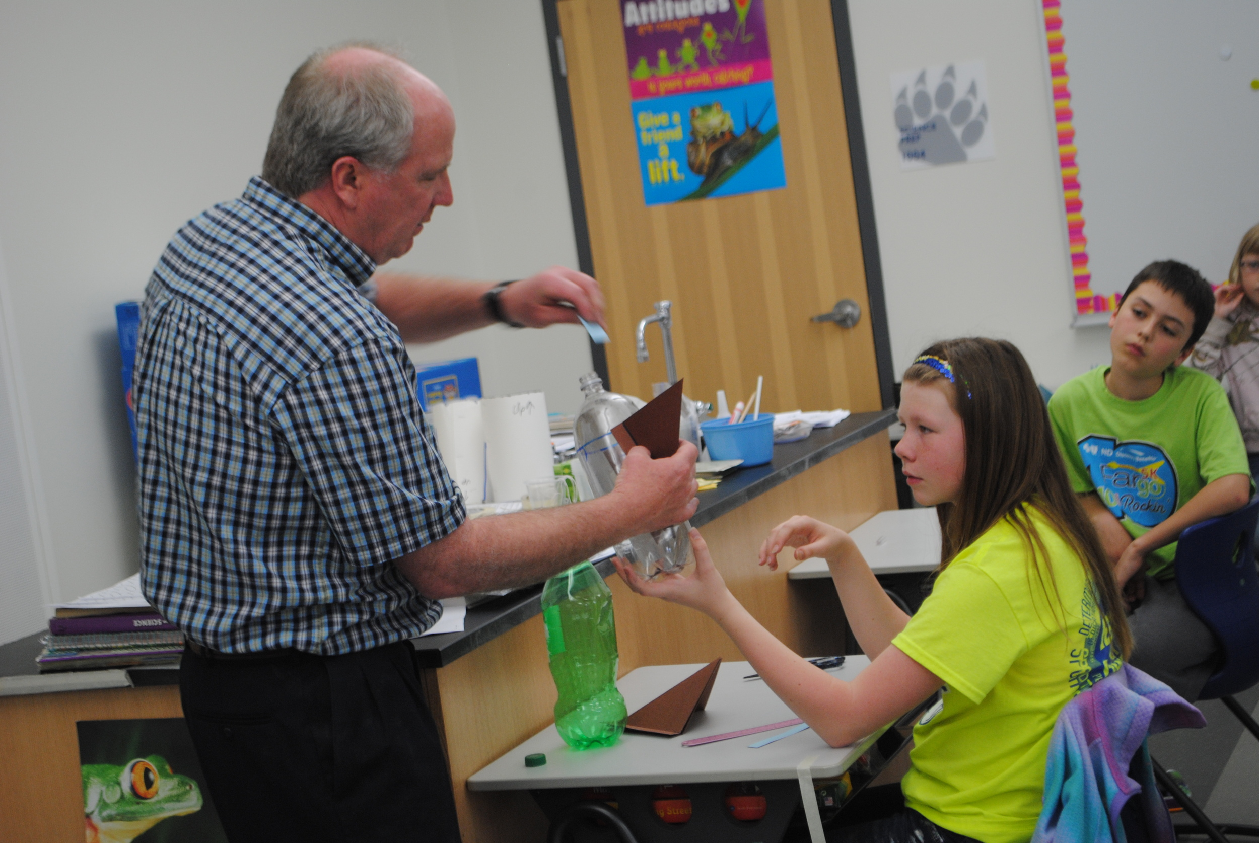 WDC fifth-grade teacher David Sea demonstrates how to put the fins on a 2-liter pop bottle during science class. Students Taliah Brown and Tony Kreklau listen to Mr. Sea's instructions. (Photos by Dana Pavek, WDC Schools)