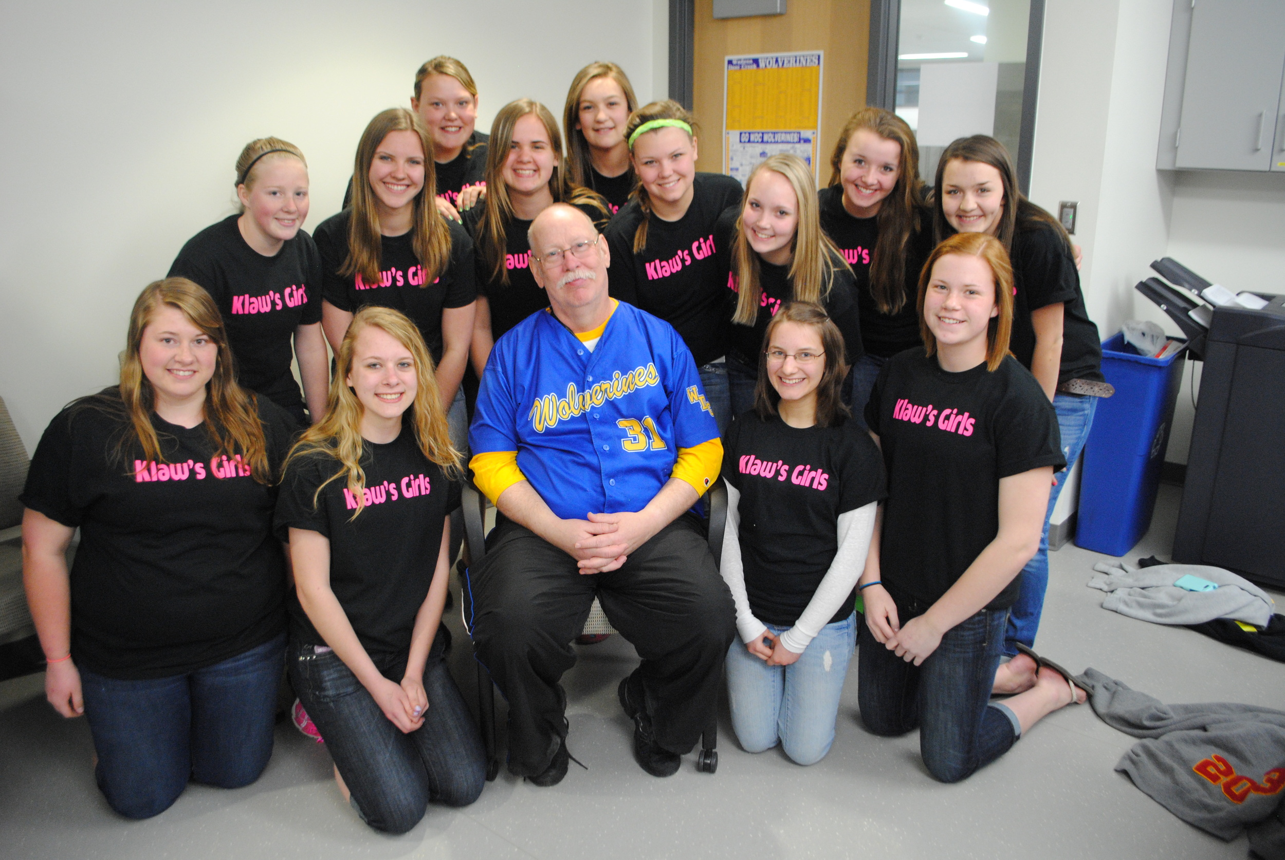 "The WDC softball varsity and JV teams had T-shirts made for game days that read, ""Klaw's Girls"" in honor of their beloved coach. Pictured with Mr. Klawitter is the JV team, from left, back row standing: Sarah Moen, Ashley Lehmkihl, Karon Johnson, Kayla Peters, Maggie Schmitz, MacKenzie Barthel, Mikena Formanek, Lauren Soroko, and Whitney Eickhoff; kneeling, from left: Kirsten Peterson, Taylor Dirks, Klawitter, Sandra Kucharczyk, and Kelsie Pierce. (Photo by Dana Pavek, WDC Schools)"