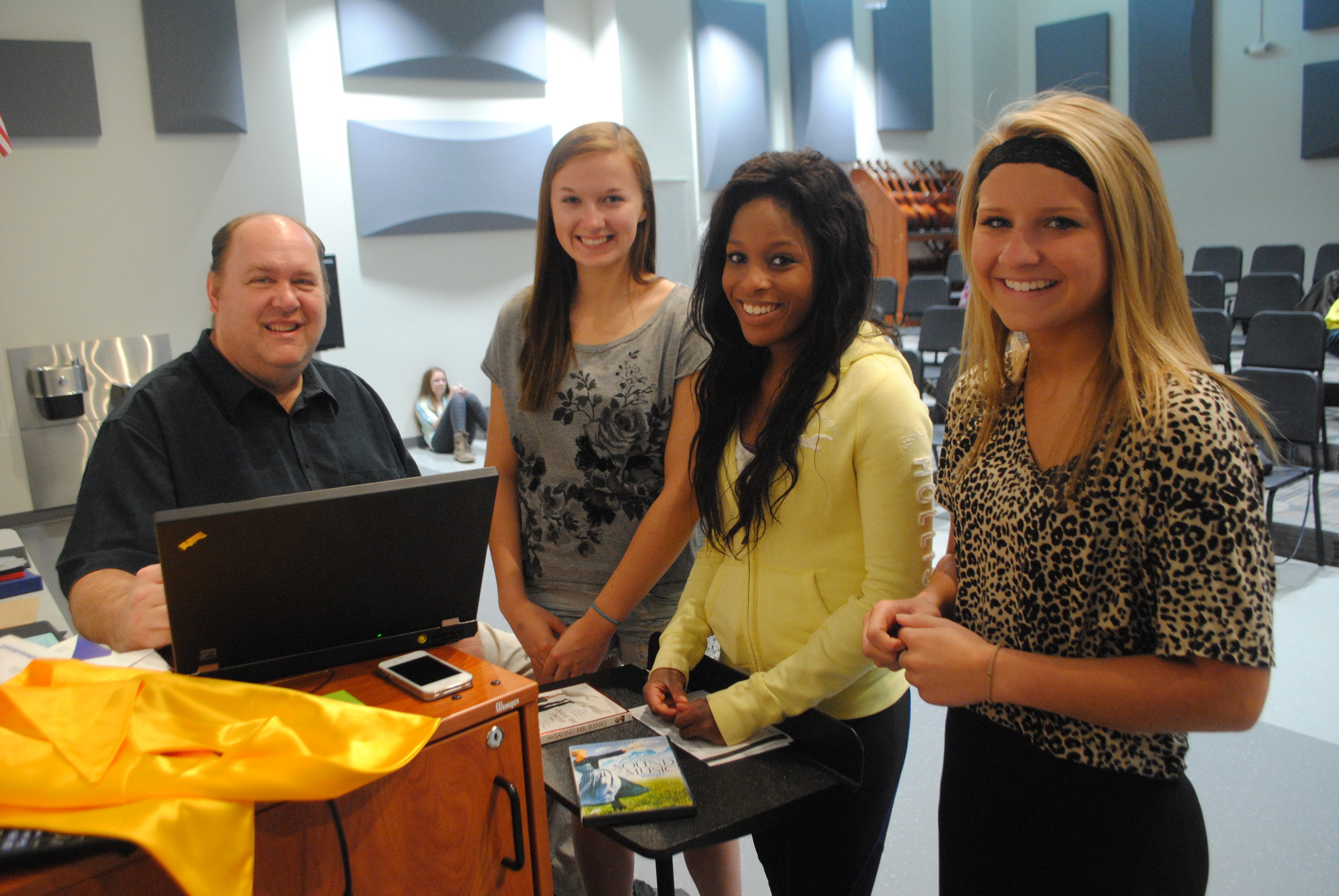 "Mike Ortmann goes over attendance with choir students Mikaela Nordlund, Lacey Malone and Madison Barthel. The students talked about how Mr. Ortmann is one of their favorite teachers. ""It's just cool,"" they said. (Photo by Dana Pavek, WDC Schools)"