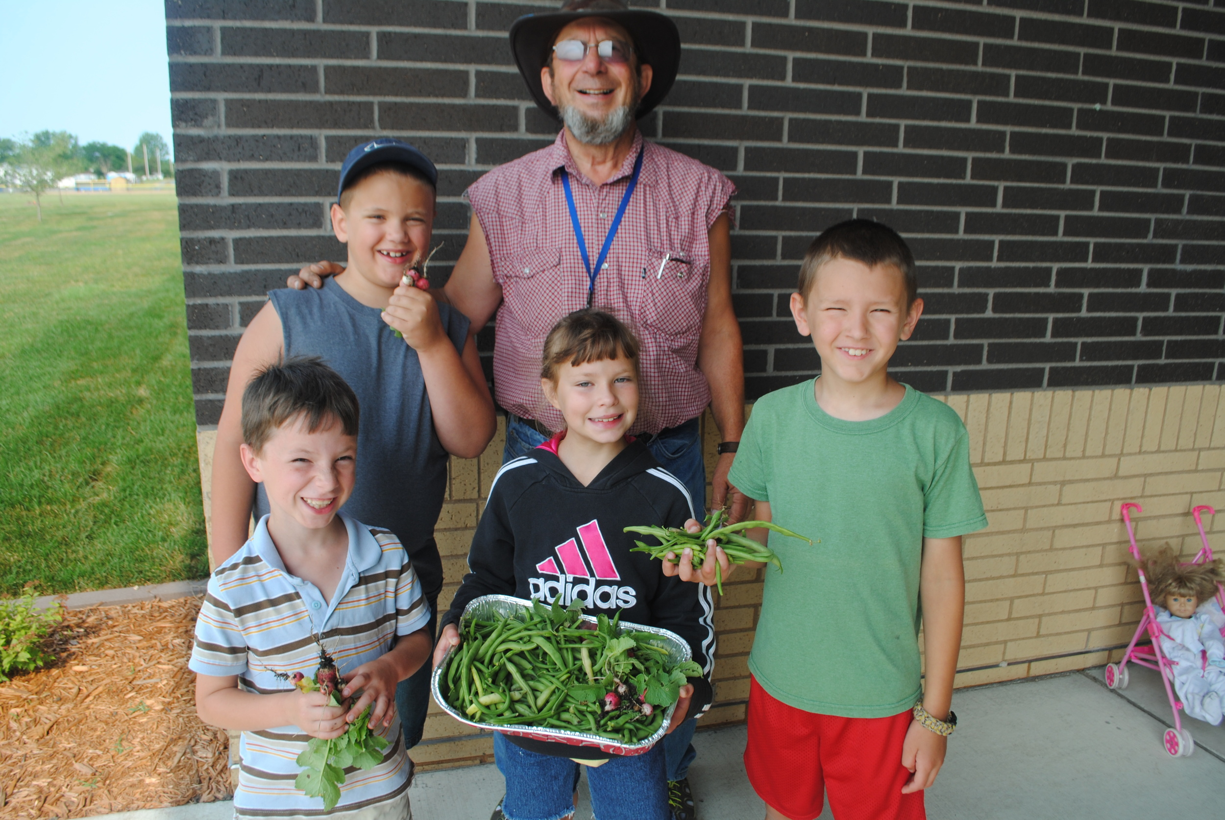"""These kids picked and delivered fresh green beans and radishes to the elementary school recently as part of a gardening class. Front, from left: Diego Shaw, Mia Shaw and Colby Schmid; back row, from left: Carter Worden and Ed Lewis, instructor. """"Harvest Time at the School Garden"""" is sponsored by WDC-B Community Education. (Photos by Dana Pavek, WDC Schools)"""