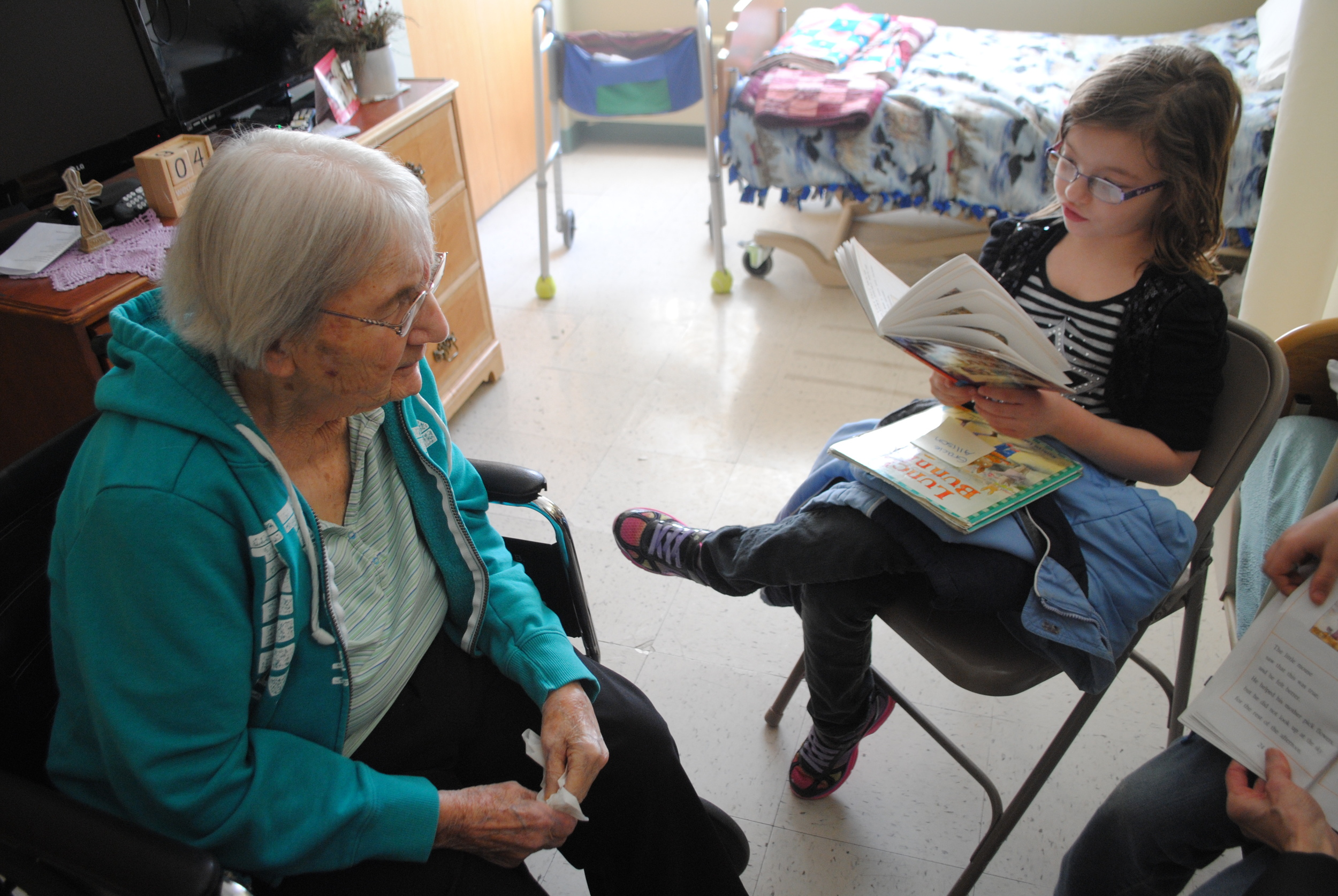 """Gracie Ames, right, reads """"Mouse Tales"""" to Maxine Bailey, a resident at Fair Oaks Lodge."""