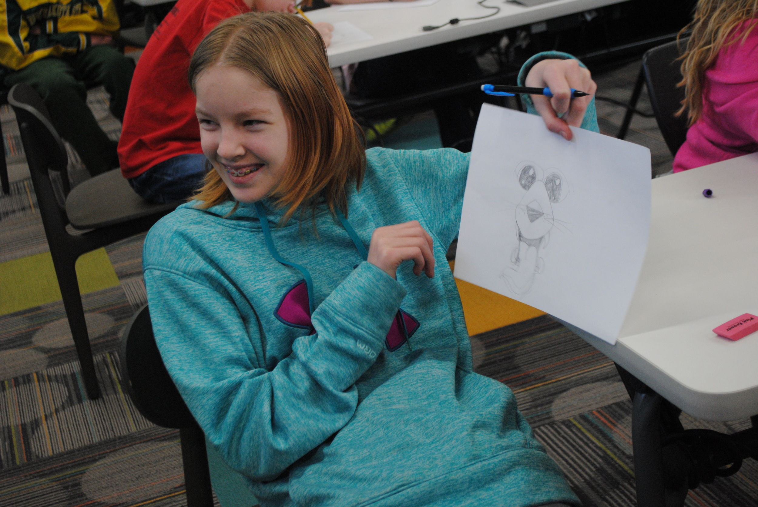 Students had fun learning how to draw an animal cartoon character, thanks to Harbo's step-by-step teaching instructions. Here, a smiling Victoria Heikkila shows a classmate her drawing during Harbo's presentation.