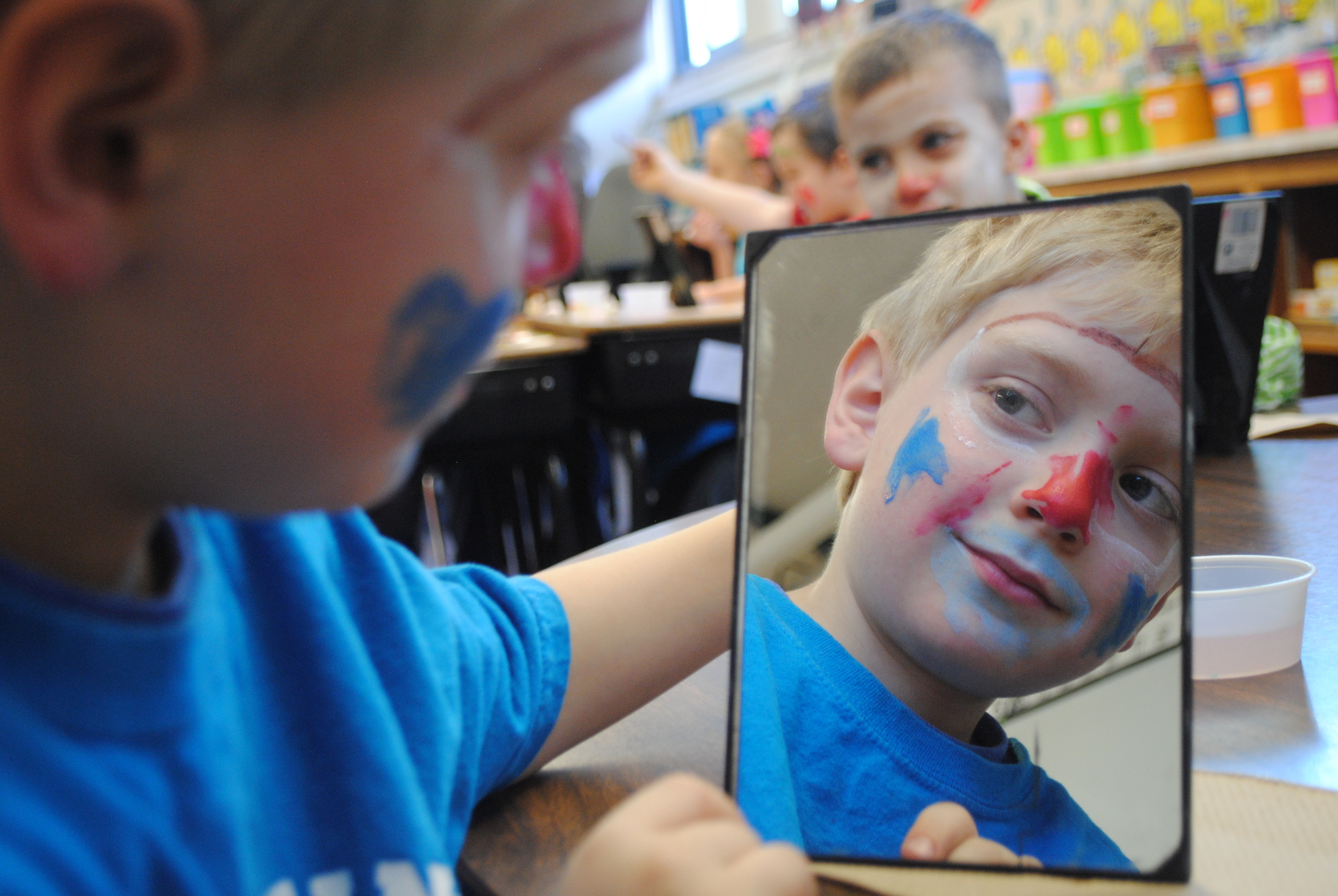 Christopher Davis admires his handiwork while applying clowning make-up on Friday, March 13. First-graders were getting ready for their clowning performance that afternoon.