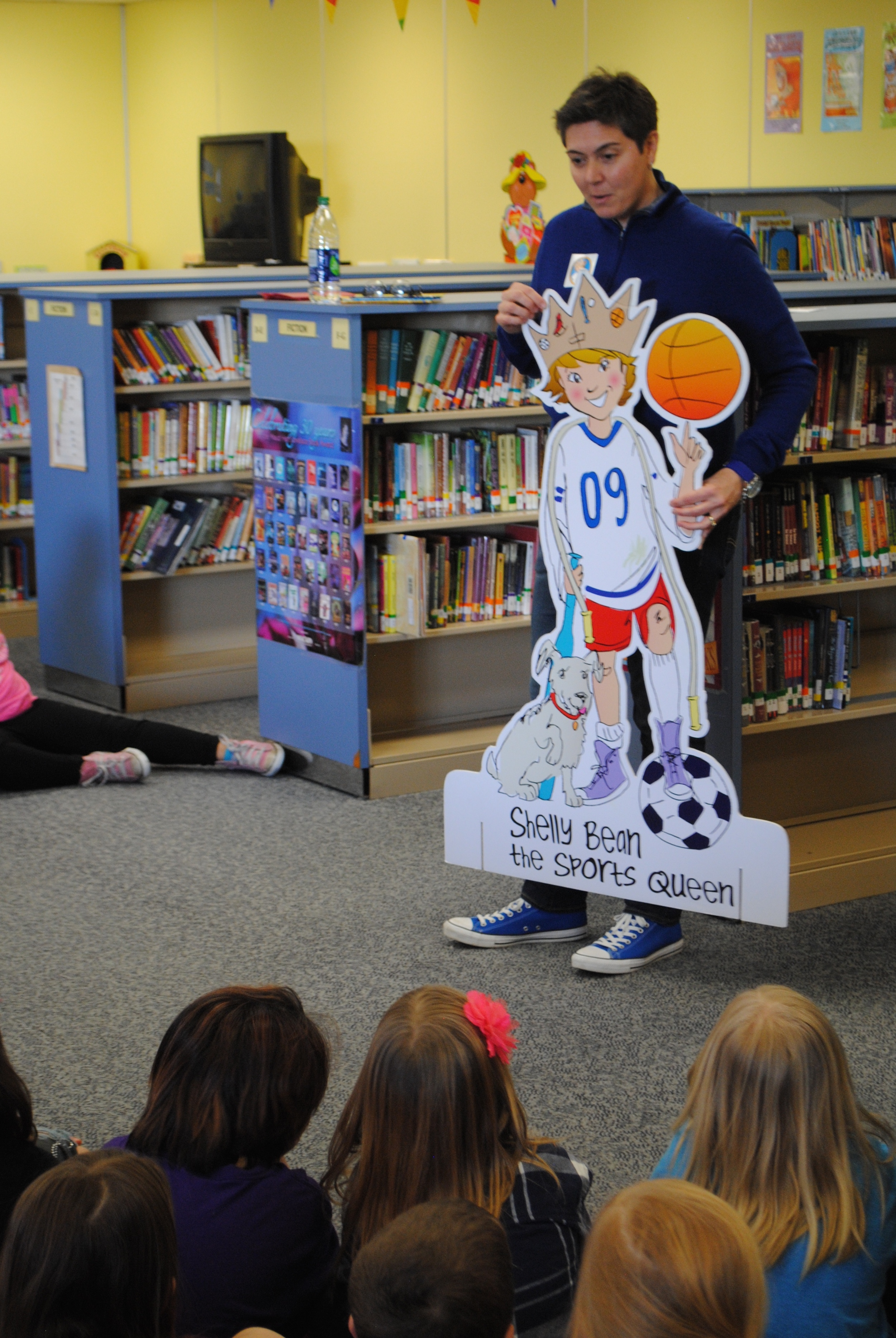 """Author Shelly Boyum-Breen shows Wadena-Deer Creek students a cardboard cutout of Shelly Bean -- a sporty, dirty-kneed little girl with a """"can-do"""" spirit."""