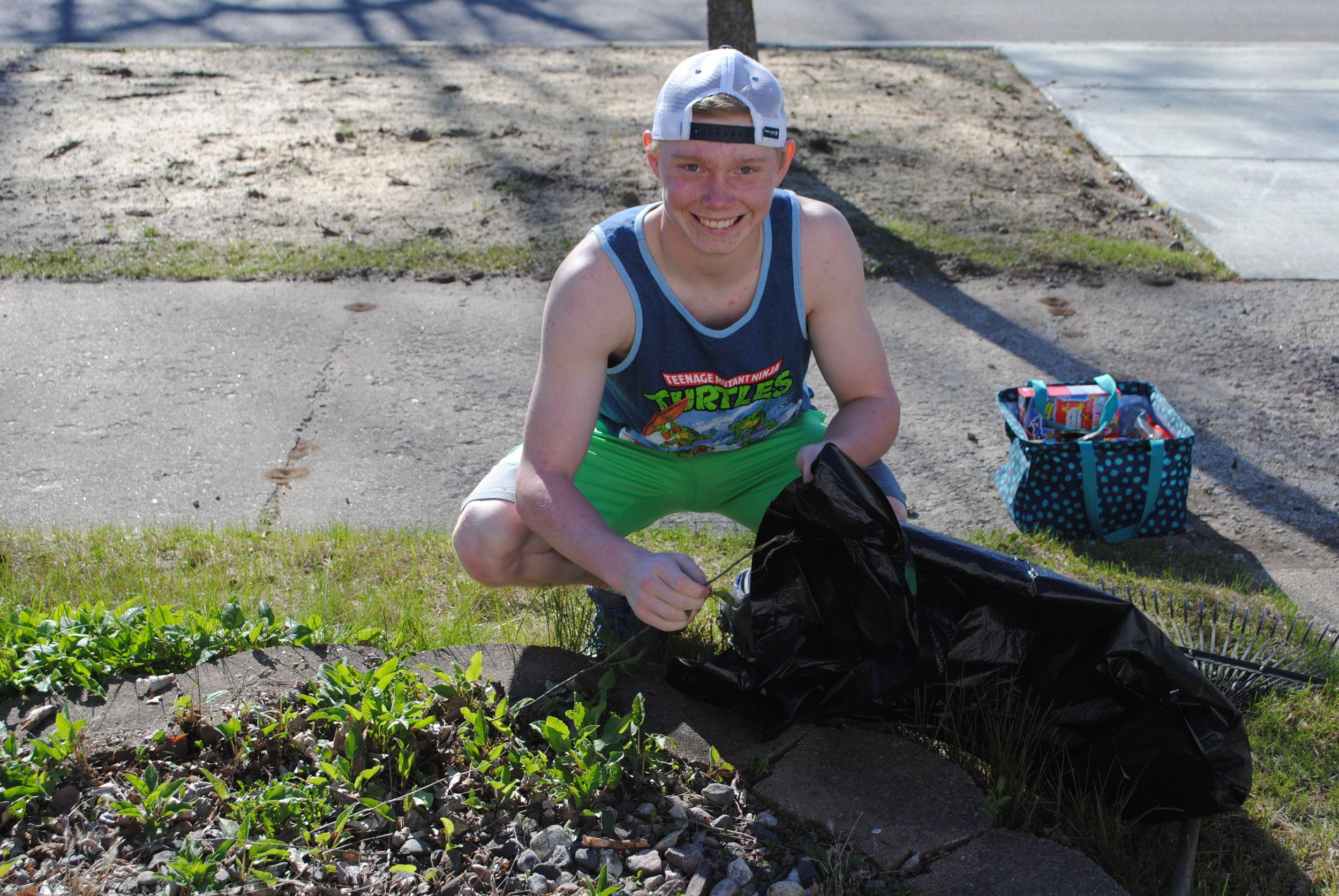 Preston Warren cleans a flower garden for an elderly resident last year.