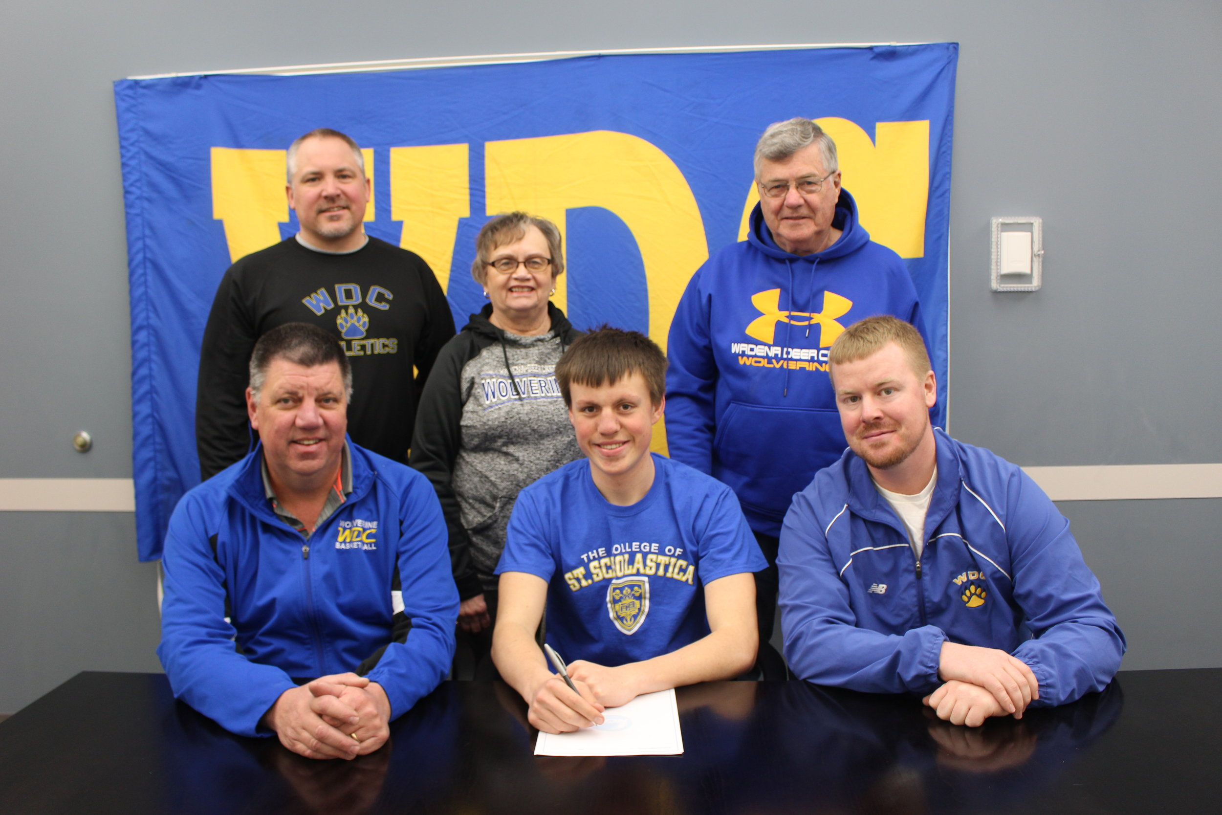 WDC's Noah Ross signing his letter of intent to play basketball at the College of St. Scholastica in Duluth. At left, sitting, is Noah's dad, Kevin, and at right, Noah's high school basketball coach, Kevin Tumberg. Back, middle and right, are Noah's grandparents, Nina and Jim Overland, and at left, Norm Gallant, WDC Activities Director.