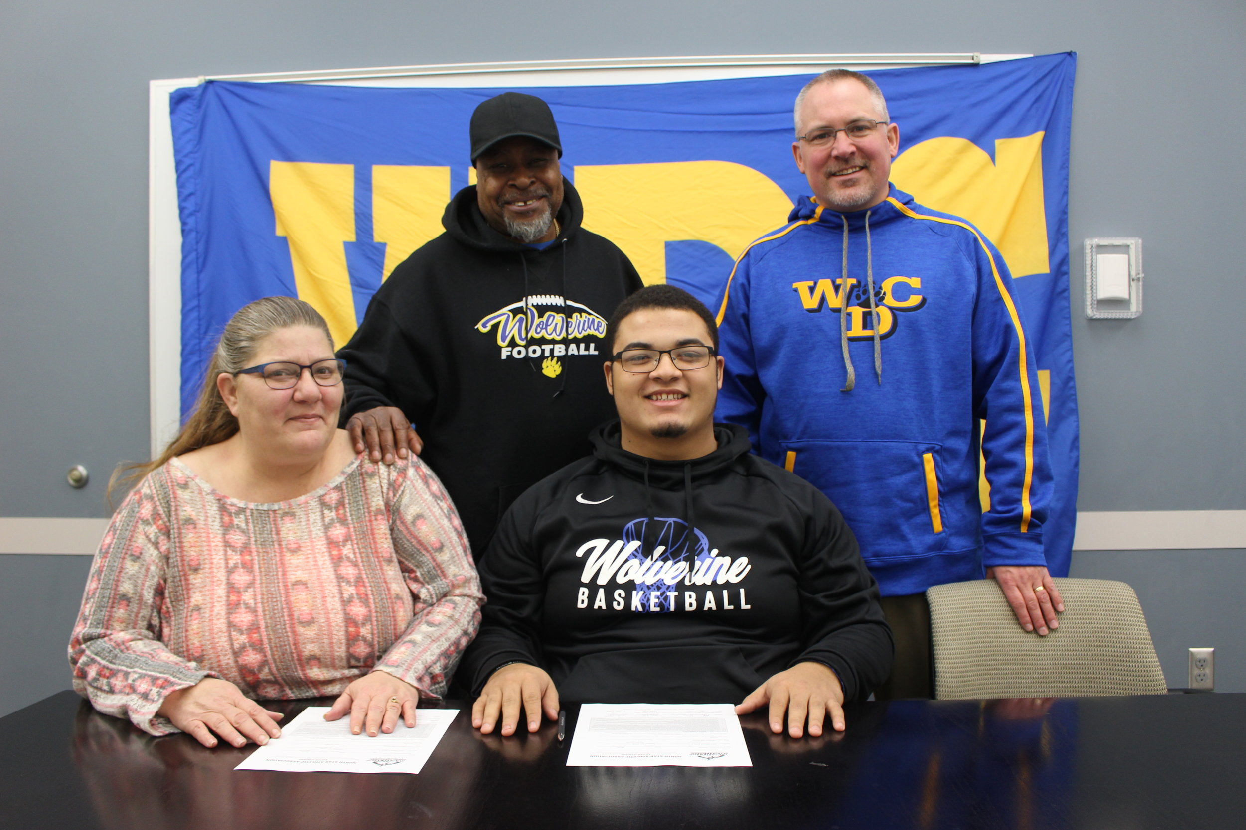 Pictured at the signing, sitting: Steven Thomas and his mom, Victoria Hunt; standing, from left, Abra Hunt, Steven's dad, and Norm Gallant, WDC activities director/assistant football coach. Signing photos by Dana Cantleberry, WDC Schools.