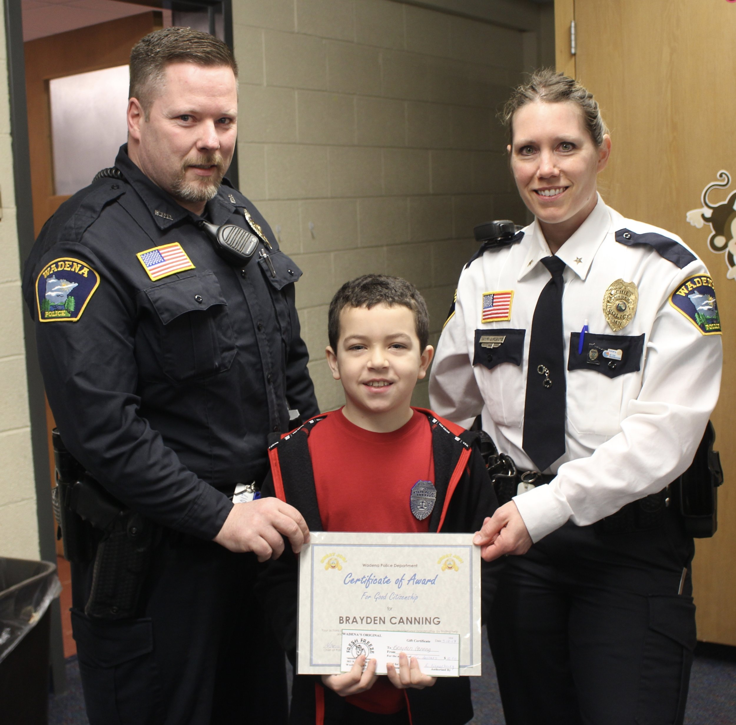 Wadena-Deer Creek second-grader Brayden Canning displays his Citizenship Award presented to him by Wadena Police Chief Naomi Plautz, right, and School Resource Officer Nick Grabe for his quick thinking and bravery. Photo by Dana Cantleberry, WDC Schools.