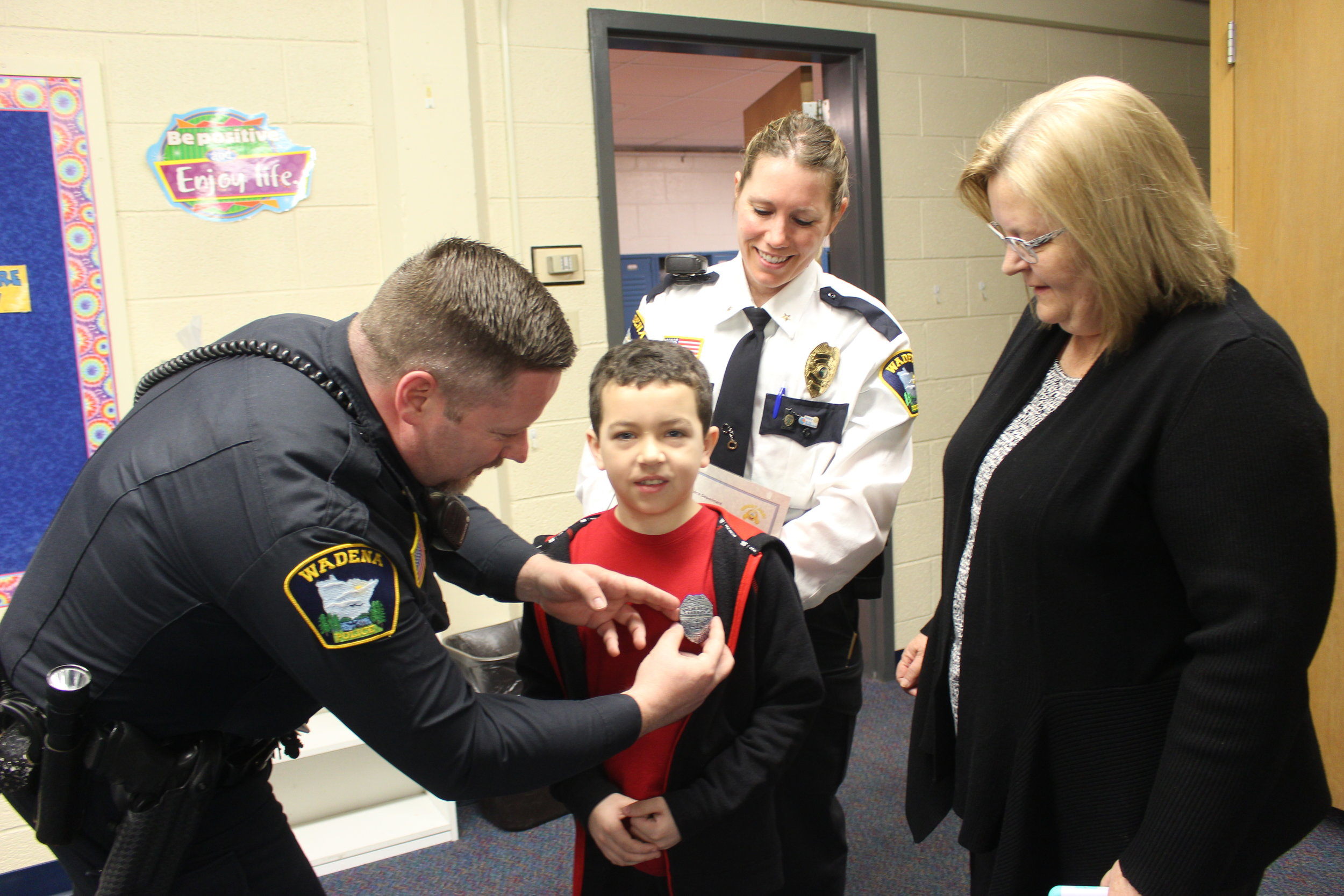 """Officer Nick Grabe pins on a """"deputy badge"""" for Brayden Canning's heroic actions in saving his 91-year-old great-grandma's life. Looking on is Brayden's grandma, Pam Canning, right, and Wadena Police Chief Naomi Plautz. Photo by Dana Cantleberry, WDC Schools."""