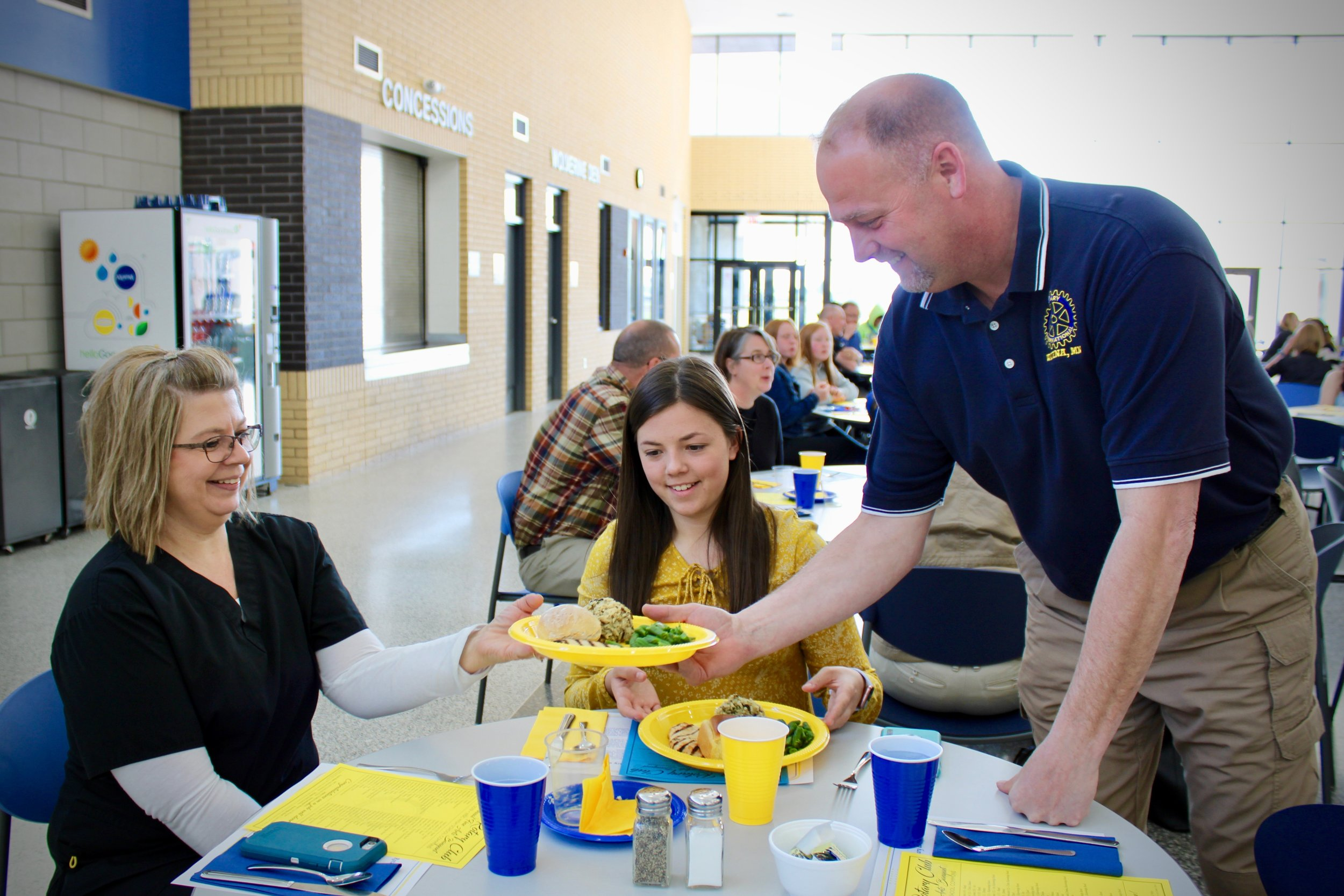 Wadena Rotarian Mike Carr Jr. serves Nancy Pierce and her daughter Lexi, a Junior honored that evening, a grilled chicken dinner at the 37th annual Wadena Rotary Club Fine Arts Banquet on May 6.