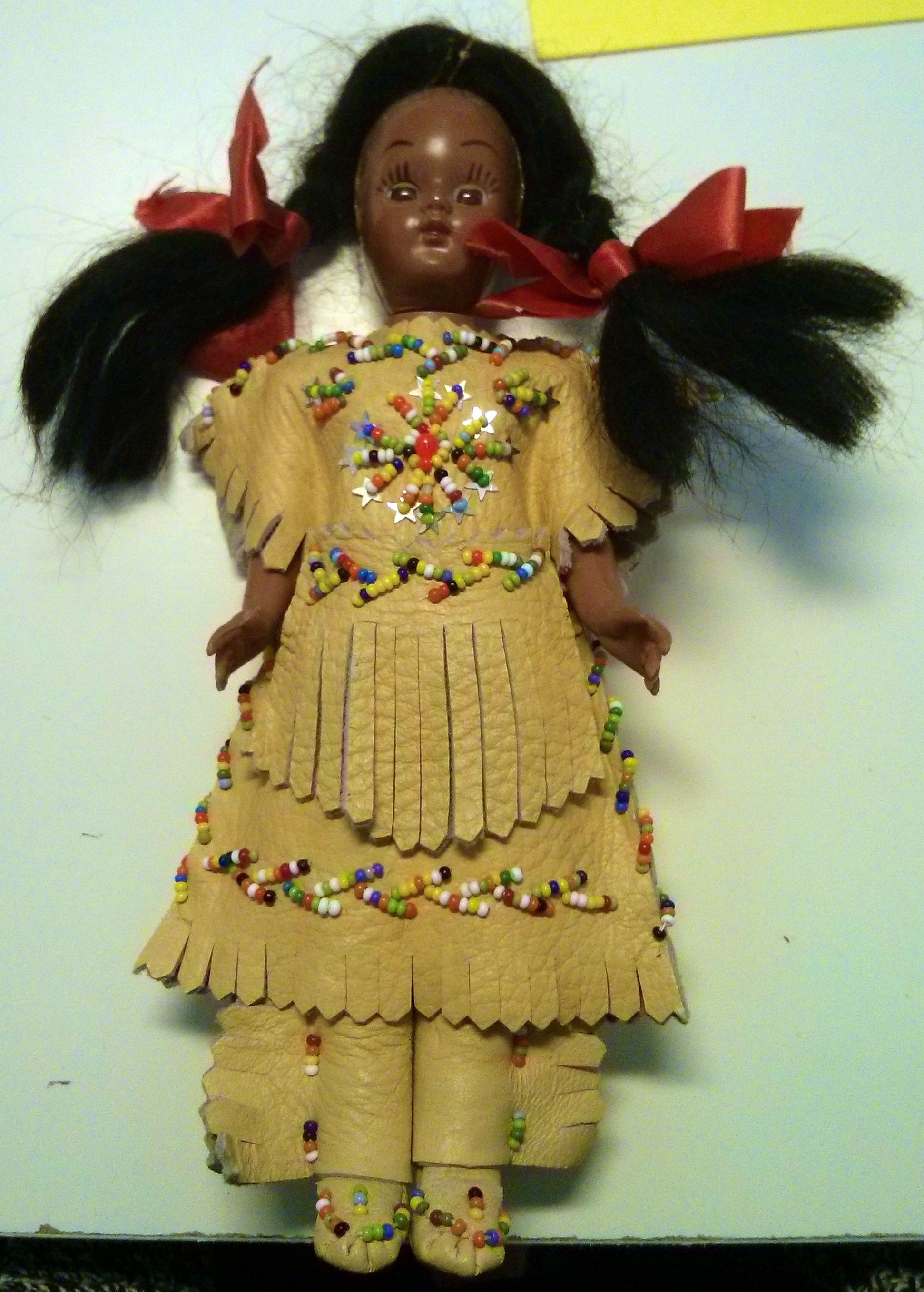 Elle perd ses cheveux la pauvre (je vais les recoller) et a perdu son bandeau. La poupée en tant que telle est probablement chinoise, mais ce type de vêtements ont peut-être été brodés à la main au Canada, peut-être même par de vrais Amérindiens, mais franchement peut-être pas.