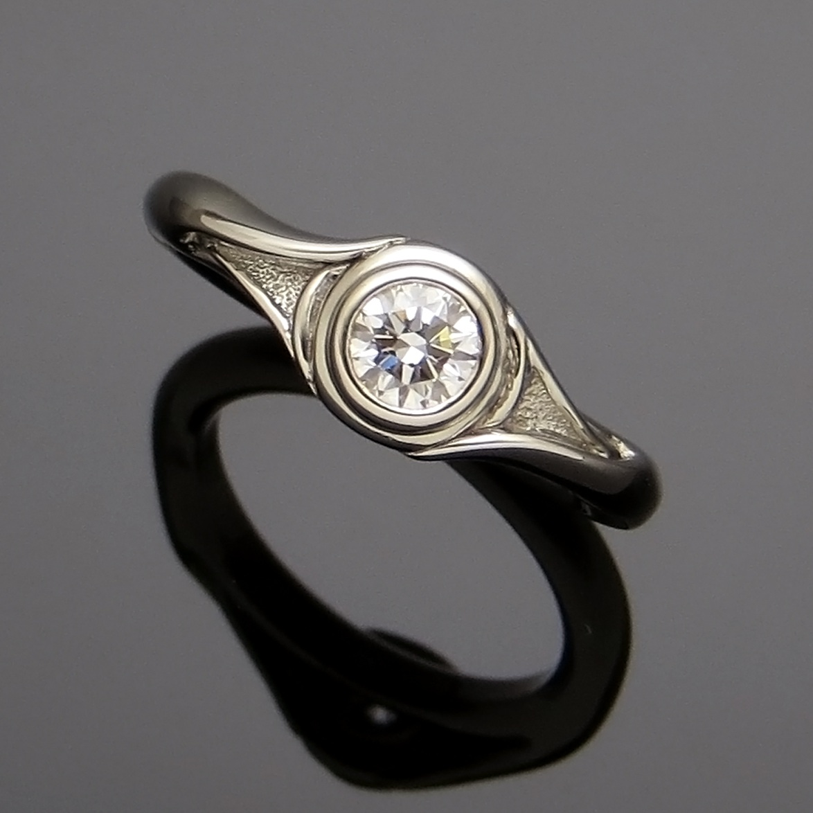 handcrafted 14k white gold engagement ring with bezel-set round brilliant diamond