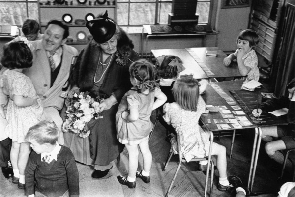 Maria Montessori and her son, Mario, visiting children in a classroom.