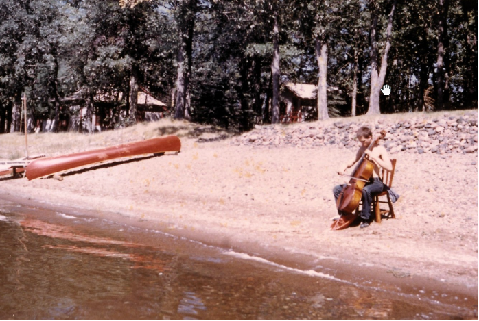 Arthur Russell playing cello on a beach in Minnesota, circa September 1971. Photograph by Charles Arthur Russell Sr. Courtesy of Charles Arthur Russell Sr. and Emily Russell.