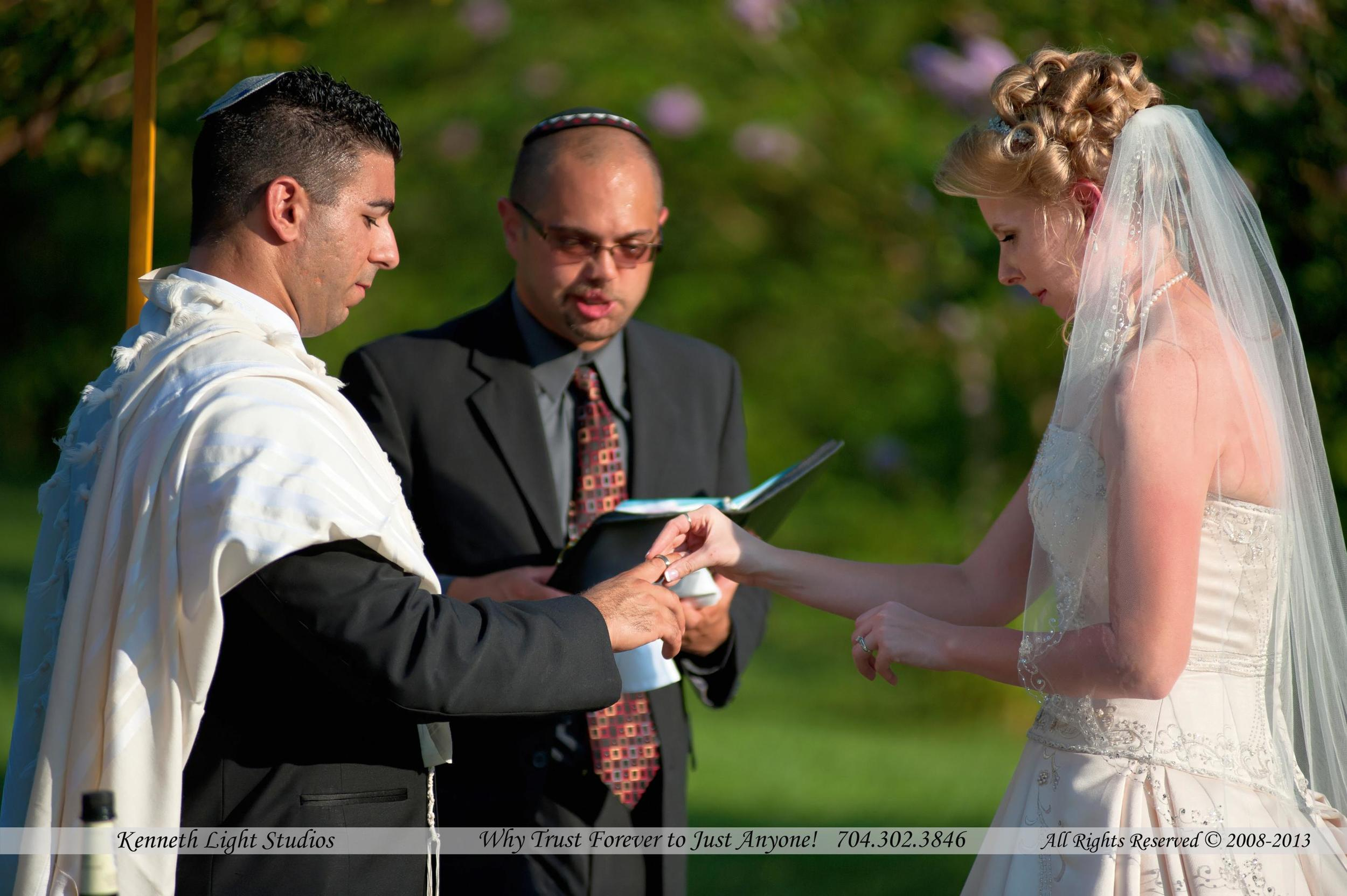 A Jewish Wedding, semi traditional, watch the ring going on the other fingers, by Kenneth Light Studios