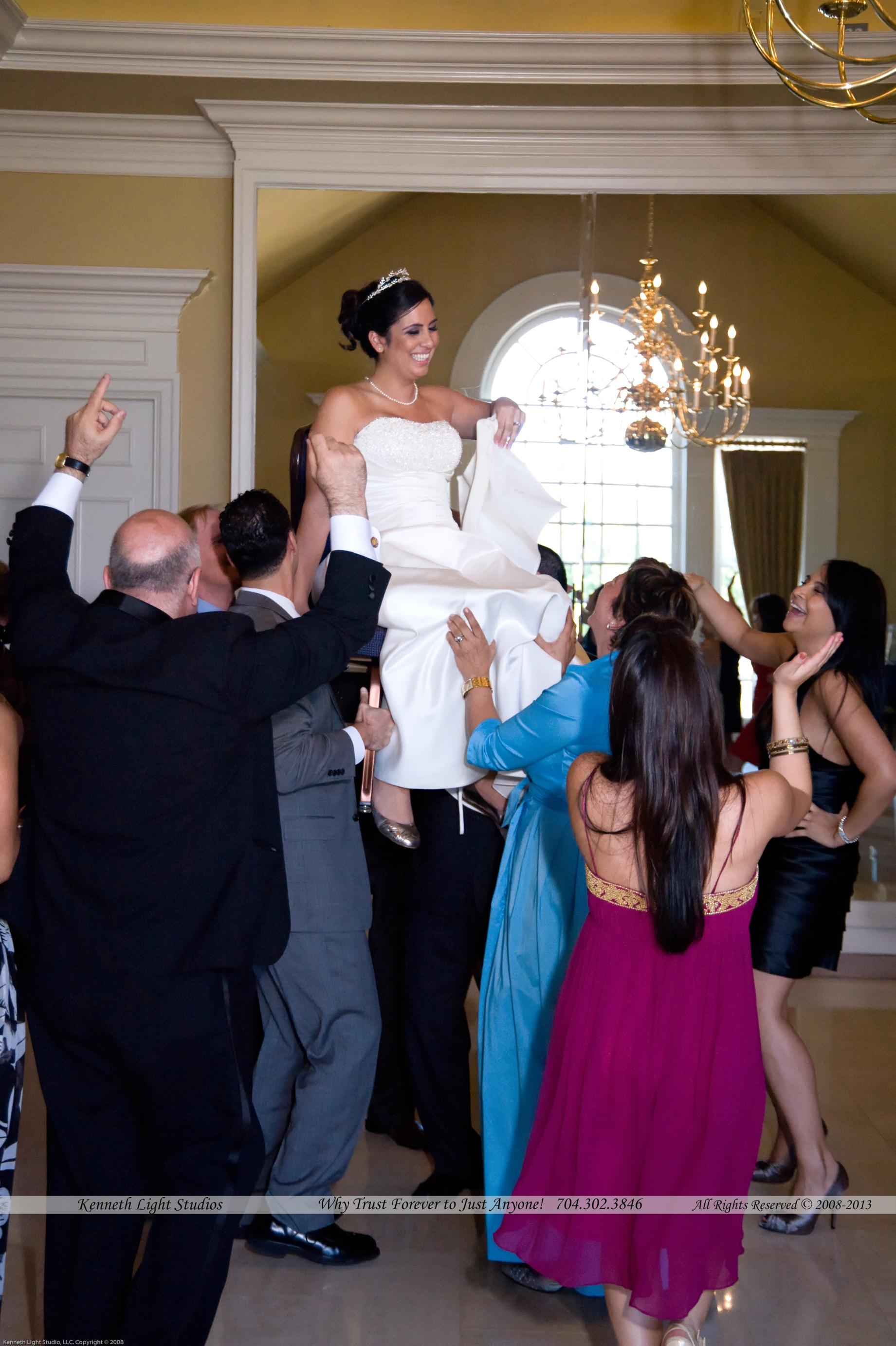 A Bride on the chair carried by her party guests on her wedding day at the providence country club in charlotte by Kenneth Light Studios
