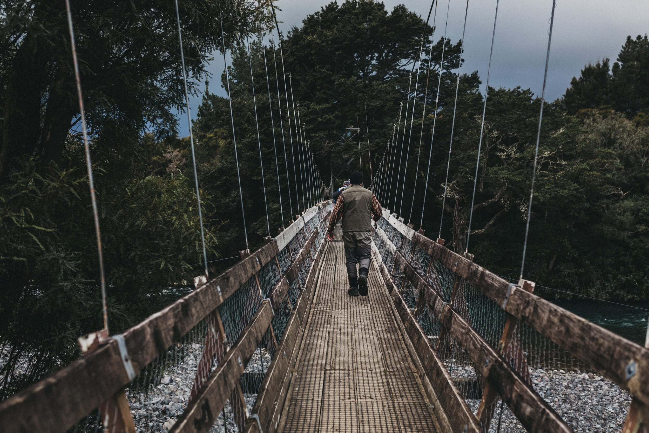 Day Two: a trout fisher crosses a bridge in Turangi with stormy skies looming.
