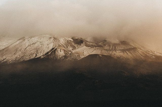 Sun setting over misty snow-capped volcanoes, Tongariro National Park, New Zealand 🌋 . . . #tongariro #tongarirocrossing #togarironationalpark #newzealand #visitnewzealand #Ngauruhoe #snow #misty #foggy #mistyfoggymilkymoody #nature #somewheremagazine #subjectivelyobjective #noicemag #melbournedocumentaryphotographer #melbournefolk #melbourneweddingphotographer #theadventurehandbook #taupo #taupovolcaniczone #pukawabay